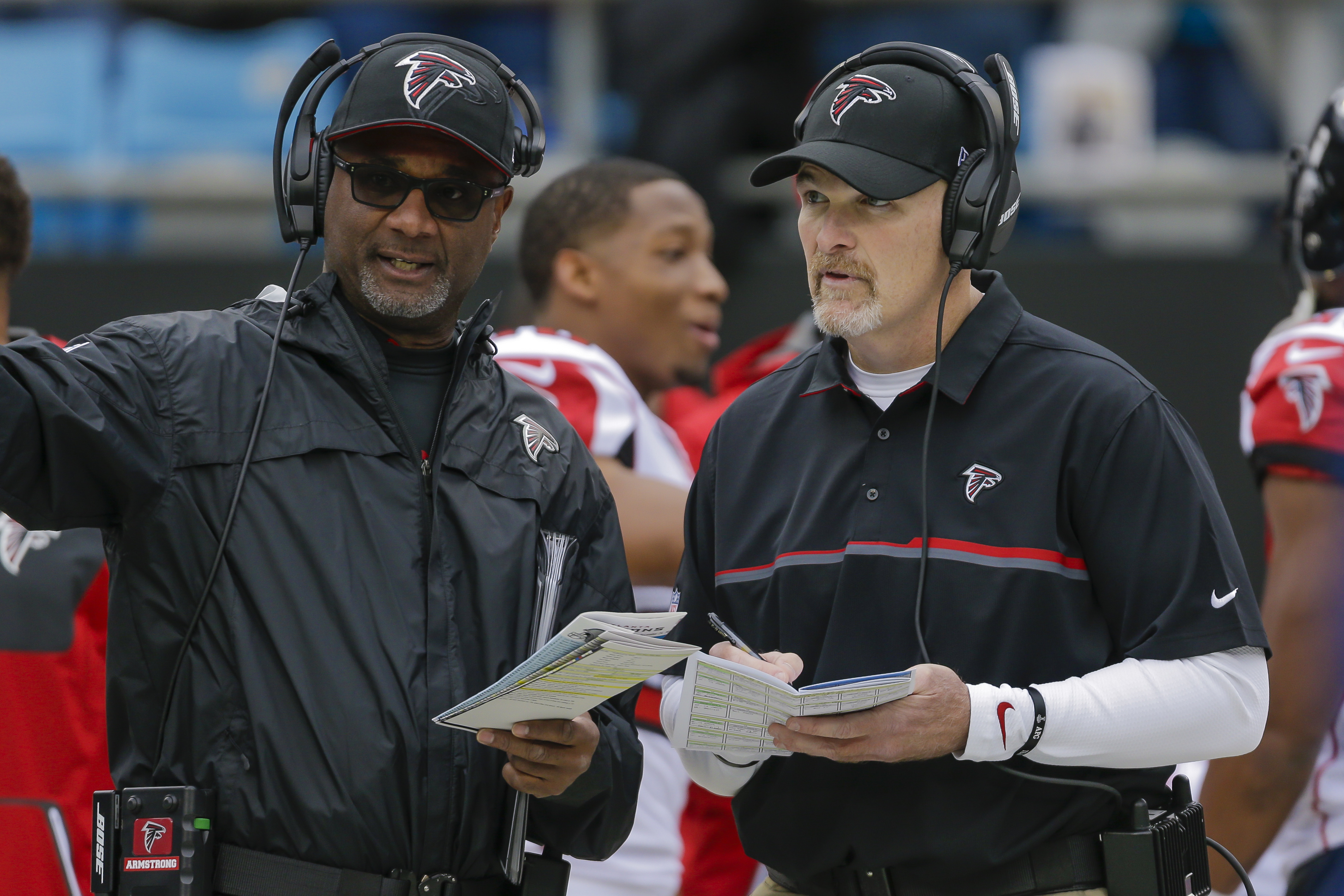 FILE - In this Dec. 24, 2016 file photo, Atlanta Falcons special teams coordinator Keith Armstrong, left, confers with head coach Dan Quinn before an NFL football game against the Carolina Panthers in Charlotte, N.C. The Atlanta Falcons have fired Armstrong, offensive coordinator Steve Sarkasian and defensive coordinator Marquand Manuel. The firings came one day after the end of the team's first losing season since 2014. Falcons owner Arthur Blank recently had said he still has confidence in Quinn and general manager Thomas Dimitroff, but changes came as expected after a 7-9 finish. (AP Photo/Bob Leverone, File)