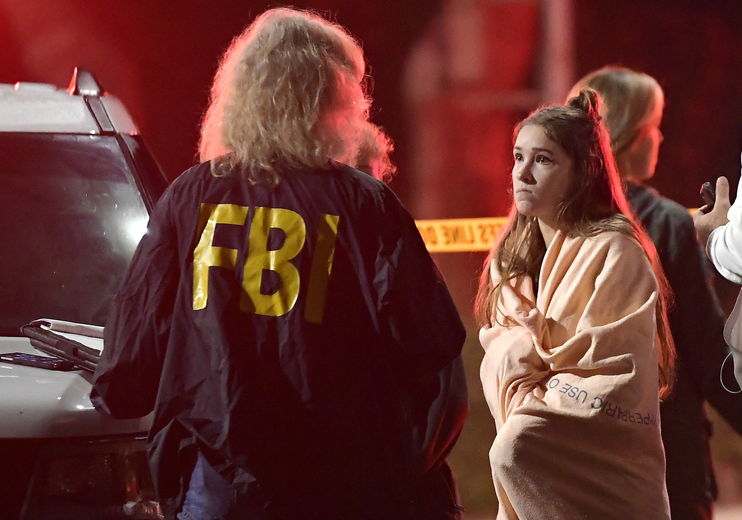 An FBI agent talks to a potential witness as they stand near the scene Thursday, Nov. 8, 2018, in Thousand Oaks, Calif. where a gunman opened fire Wednesday inside a country dance bar crowded with hundreds of people on