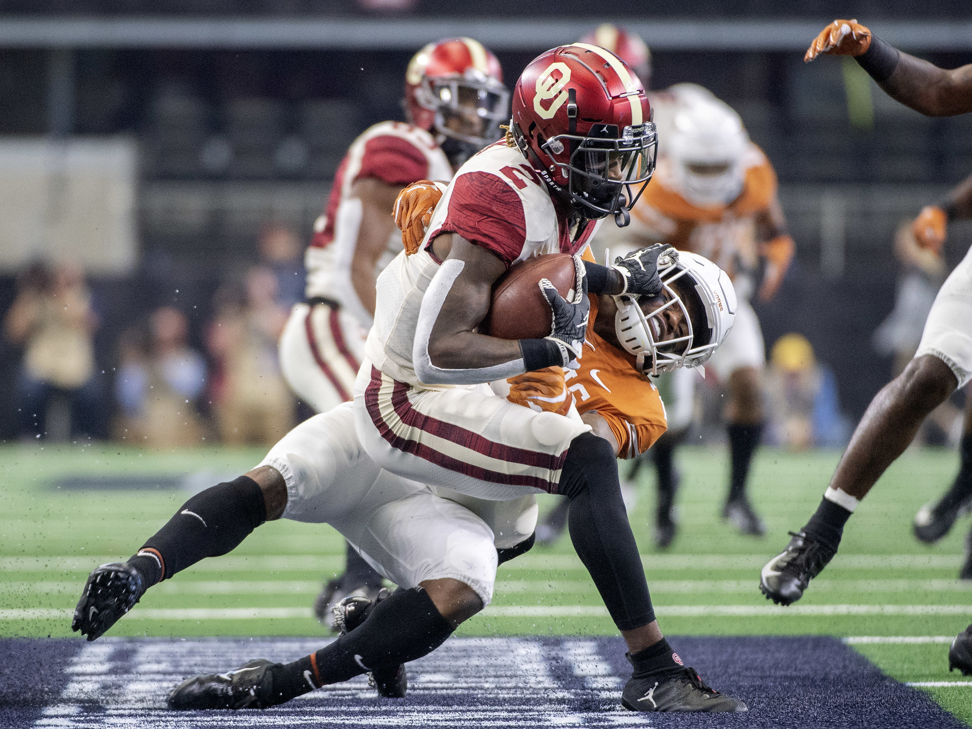 Texas defensive back Josh Thompson (29) brings down Oklahoma punt returner CeeDee Lamb (2) on a punt return during the first half of the Big 12 Conference championship NCAA college football game on Saturday, Dec. 1, 2018, in Arlington, Texas. (AP Photo/Jeffrey McWhorter)