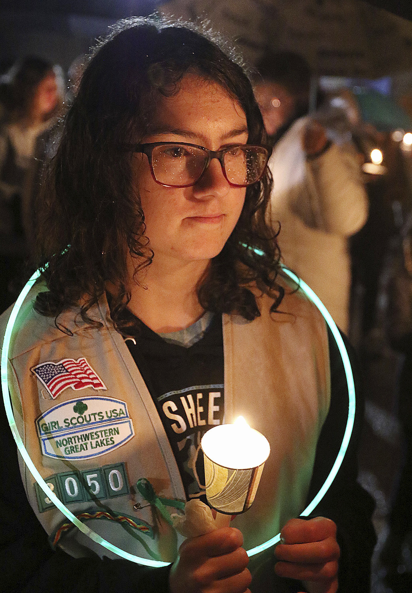 Girl Scout Jessica Lauterbach, 12, of Altoona, Wis., attends a candlelight vigil at Halmstad Elementary School in Chippewa Falls, Wis., Sunday evening, Nov. 4, 2018, in remembrance of three fourth grade Girl Scouts and a parent who died Saturday, after being struck by a pickup truck while their troop was picking up trash along a rural highway. The 21-year-old driver, Colten Treu of Chippewa Falls, sped off but later surrendered. He will be charged with four counts of homicide, Lake Hallie police Sgt. Daniel Sokup said. (Steve Kinderman/The Eau Claire Leader-Telegram via AP)