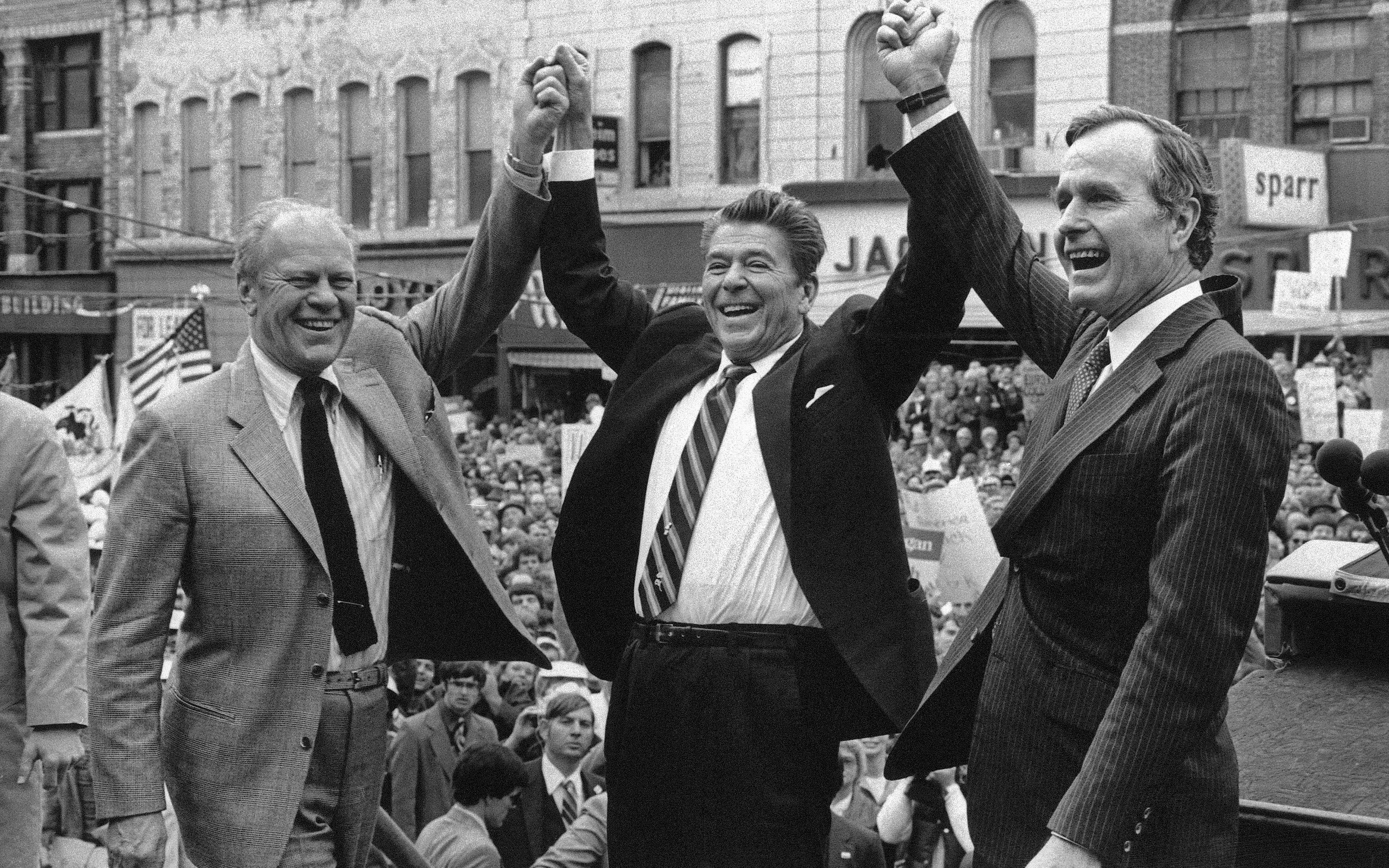 In this Nov. 3, 1980, photo, former President Gerald Ford lends his support to Republican presidential candidate Ronald Reagan and his running mate, George H.W. Bush in Peoria, Ill. (AP Photo, File)