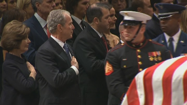 Former President George W. Bush and former first lady Laura Bush hold their hands over their hearts at George H.W. Bush.