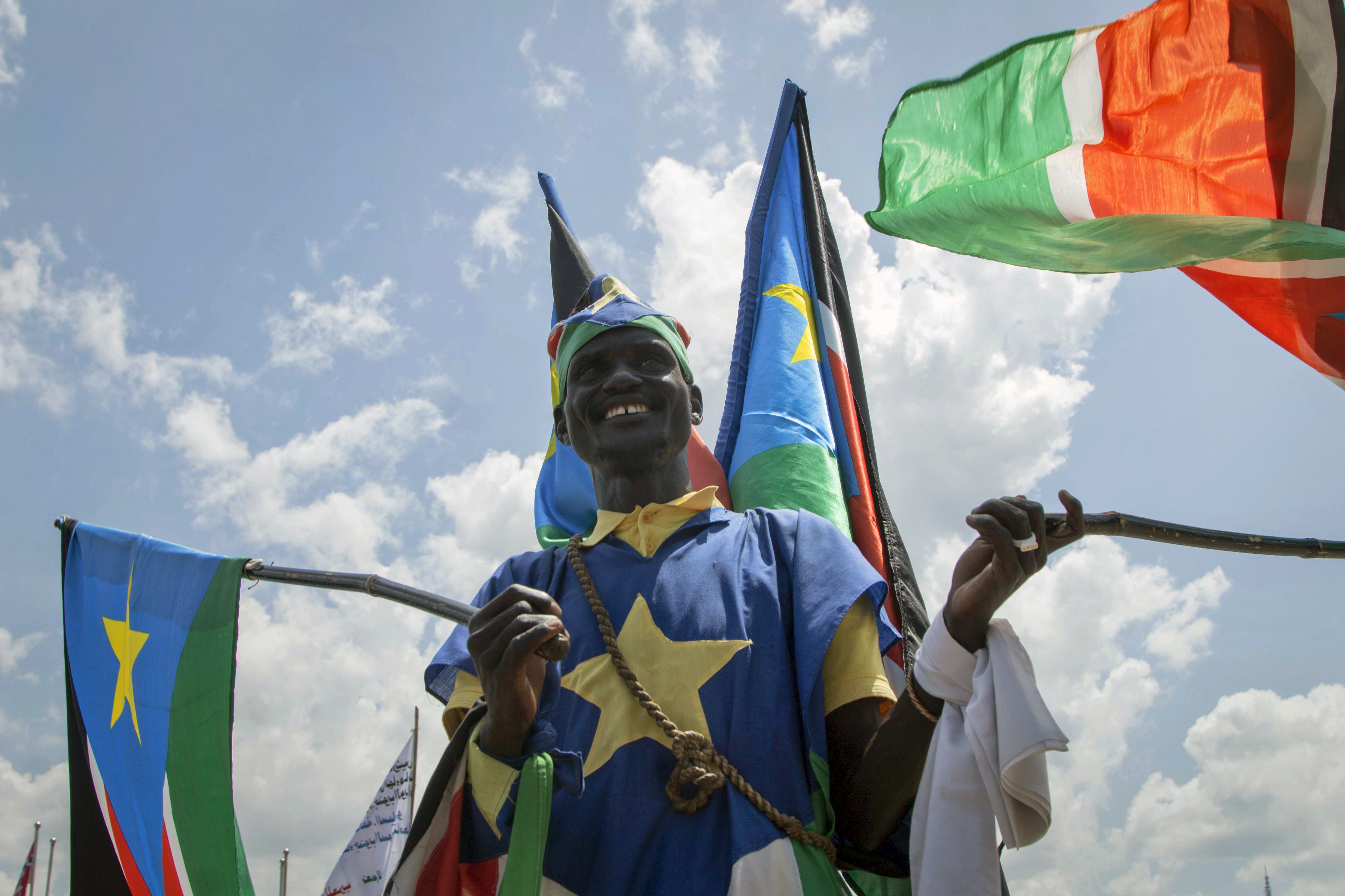 A man waves South Sudanese national flags during peace celebrations in the capital Juba, South Sudan Wednesday, Oct. 31, 2018. For the first time since fleeing South Sudan more than two years ago, opposition leader Riek Machar returned on Wednesday to take part in a nationwide peace celebration. (AP Photo/Bullen Chol)