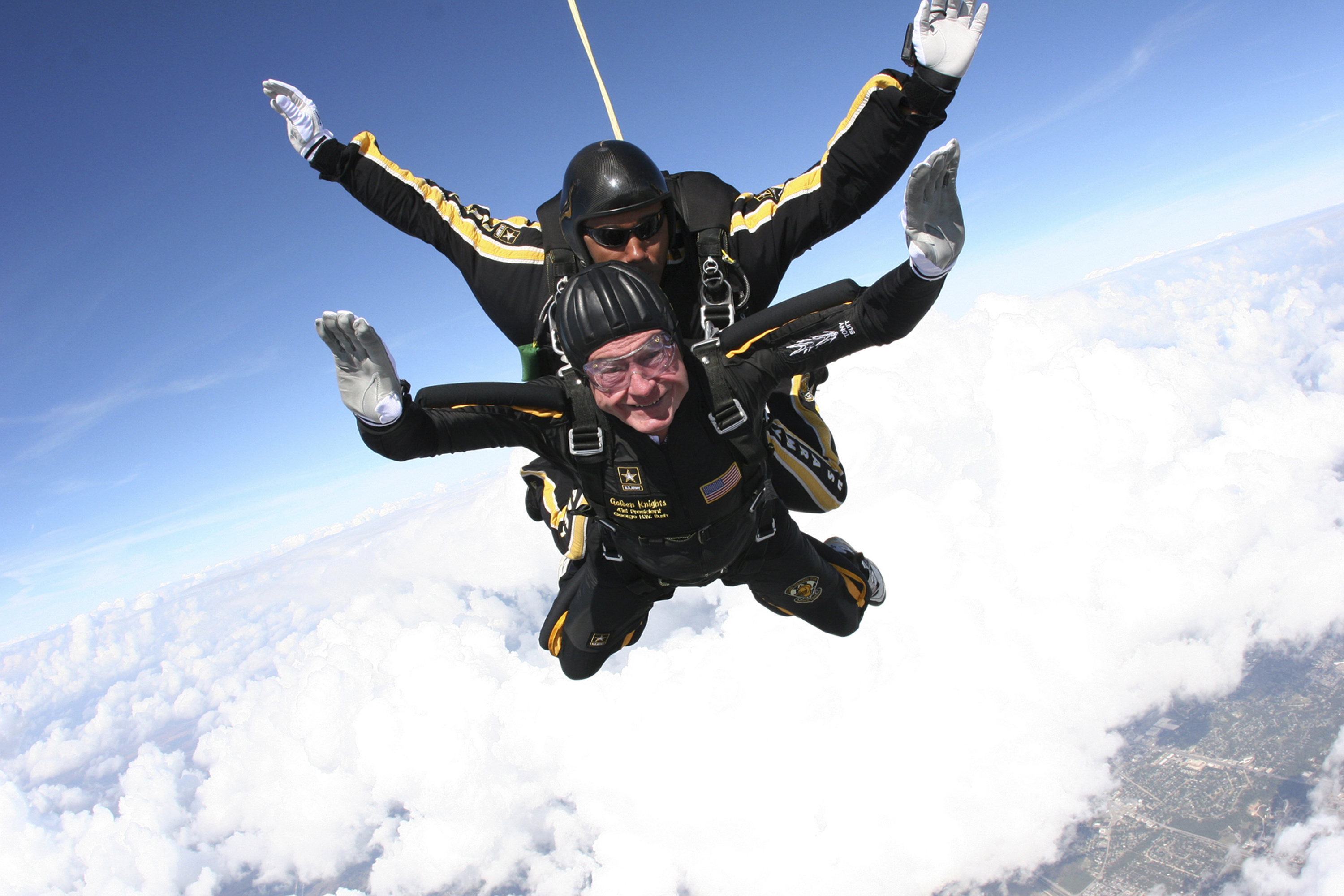 In this Nov. 10, 2007, photo provided by the U.S. Army Golden Knights, former President George H.W. Bush free falls with Golden Knights parachute team member Sgt. 1st Class Mike Elliott, as he makes a dramatic entrance to his presidential museum during a rededication ceremony in College Station, Texas. (Sgt. 1st Class Kevin McDaniel/U.S. Army via AP, File)