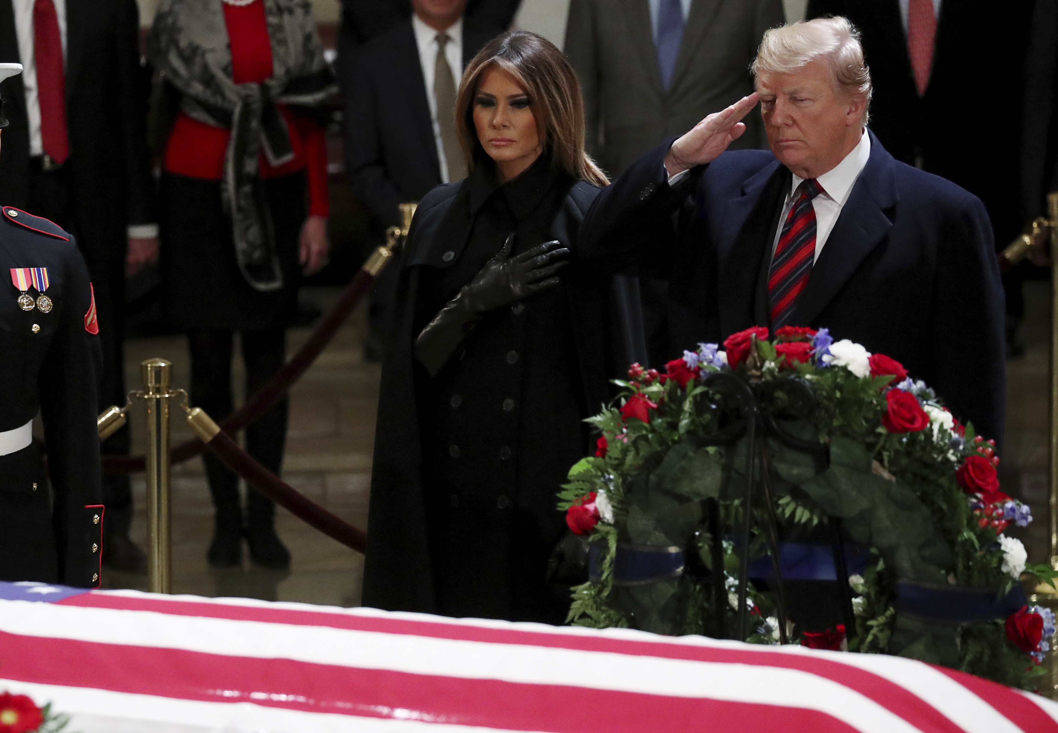 President Donald Trump salutes and first lady Melania Trump pays respects at the casket of former President George H.W. Bush as it lies in state inside the Capitol Rotunda on Capitol Hill, Monday, Dec. 3, 2018 in Washington. (Jonathan Ernst/Pool via AP)