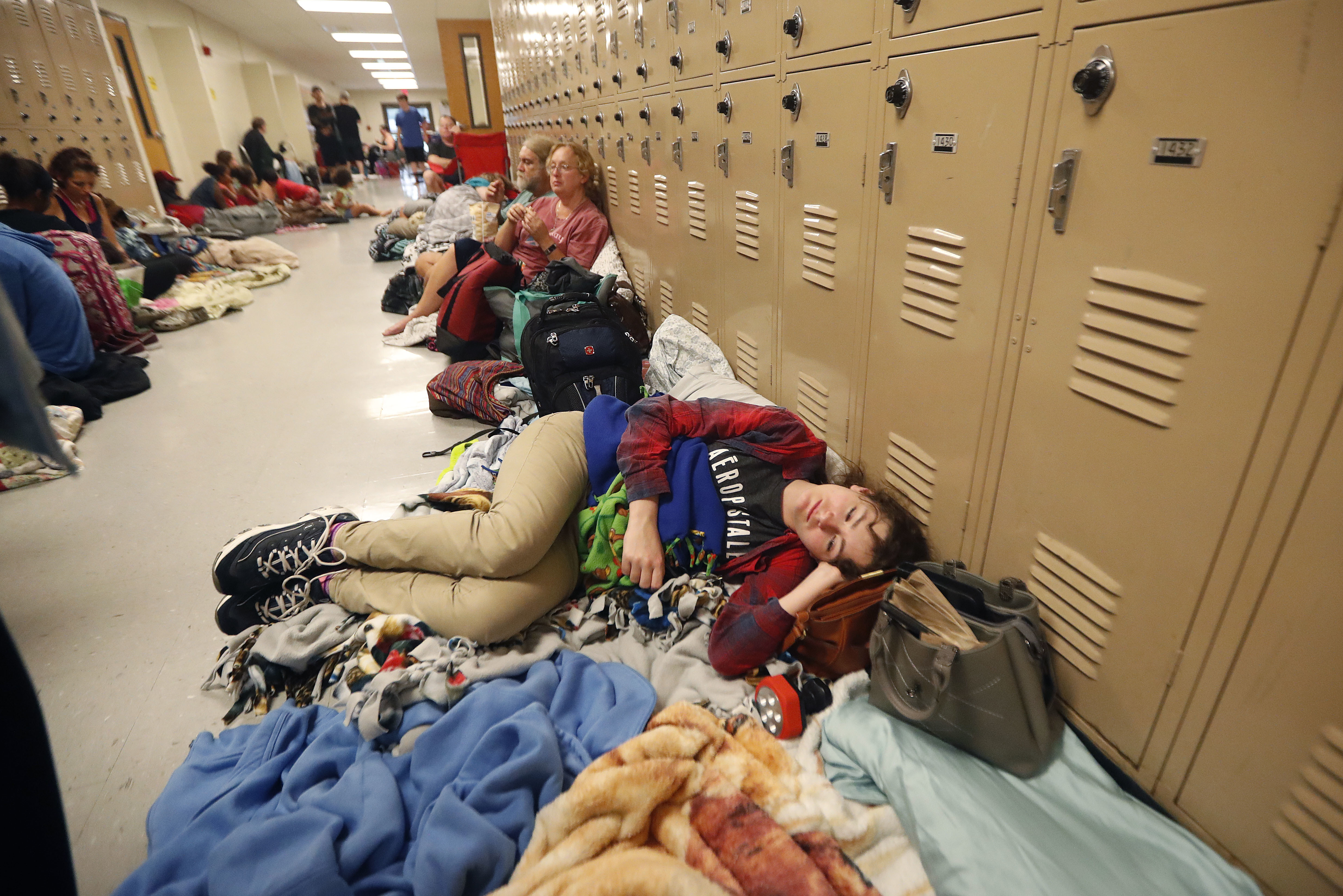 CORRECTS NAME OF HURRICANE TO MICHAEL FROM MATTHEW - Emily Hindle lies on the floor at an evacuation shelter set up at Rutherford High School, in advance of Hurricane Michael, which is expected to make landfall today, in Panama City Beach, Fla., Wednesday, Oct. 10, 2018. (AP Photo/Gerald Herbert)