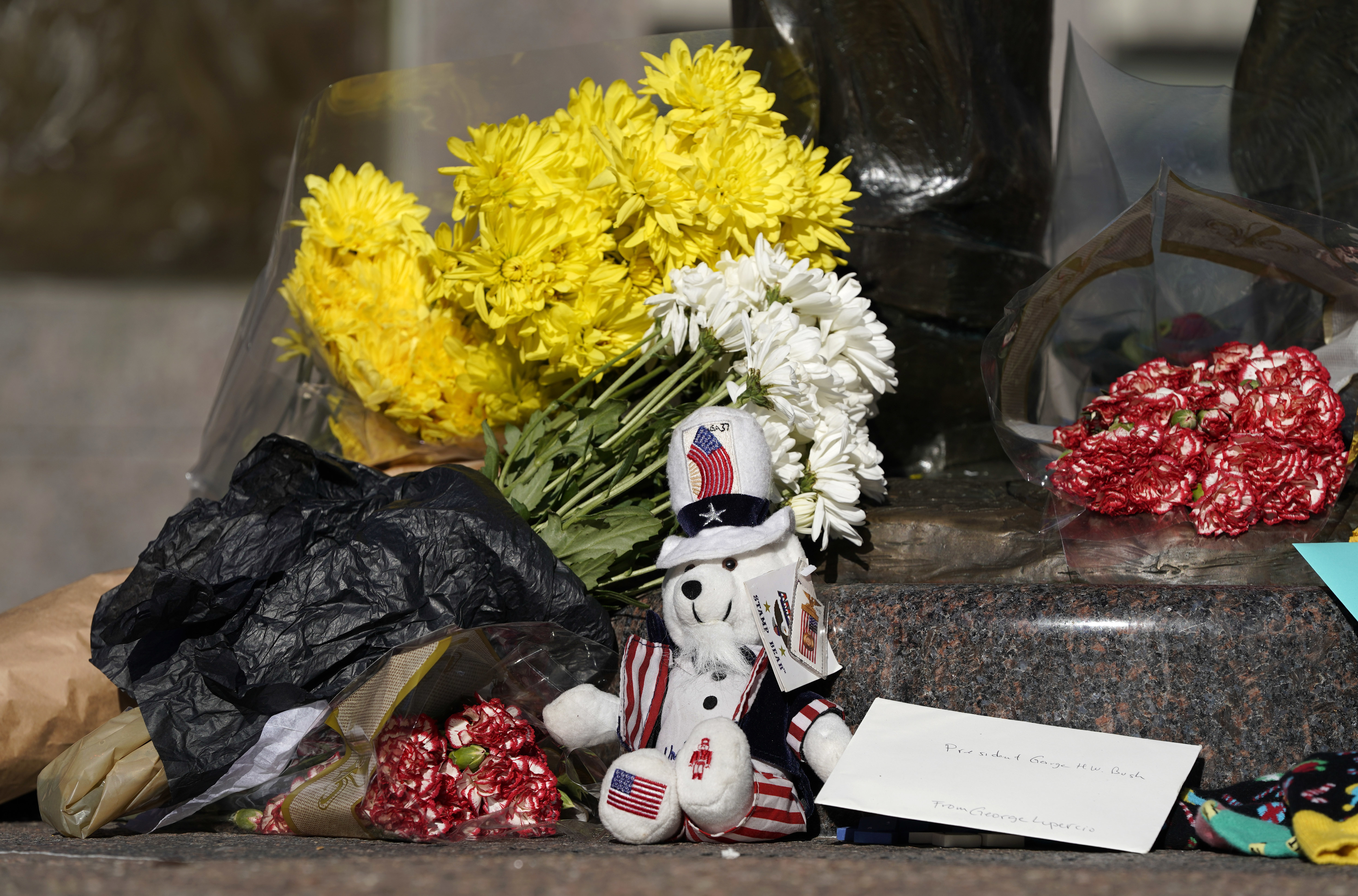 A makeshift memorial is shown at the base of a statue of former President George H.W. Bush in downtown Houston, Sunday, Dec. 2. (AP Photo/David J. Phillip)