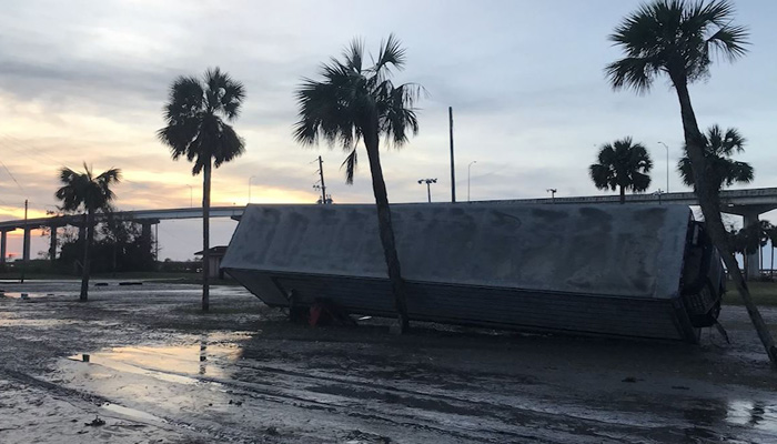 A trailer leans against palm trees in Apalachicola, FL, after powerful Hurricane Michael made landfall in the Florida Panhandle on Wednesday.