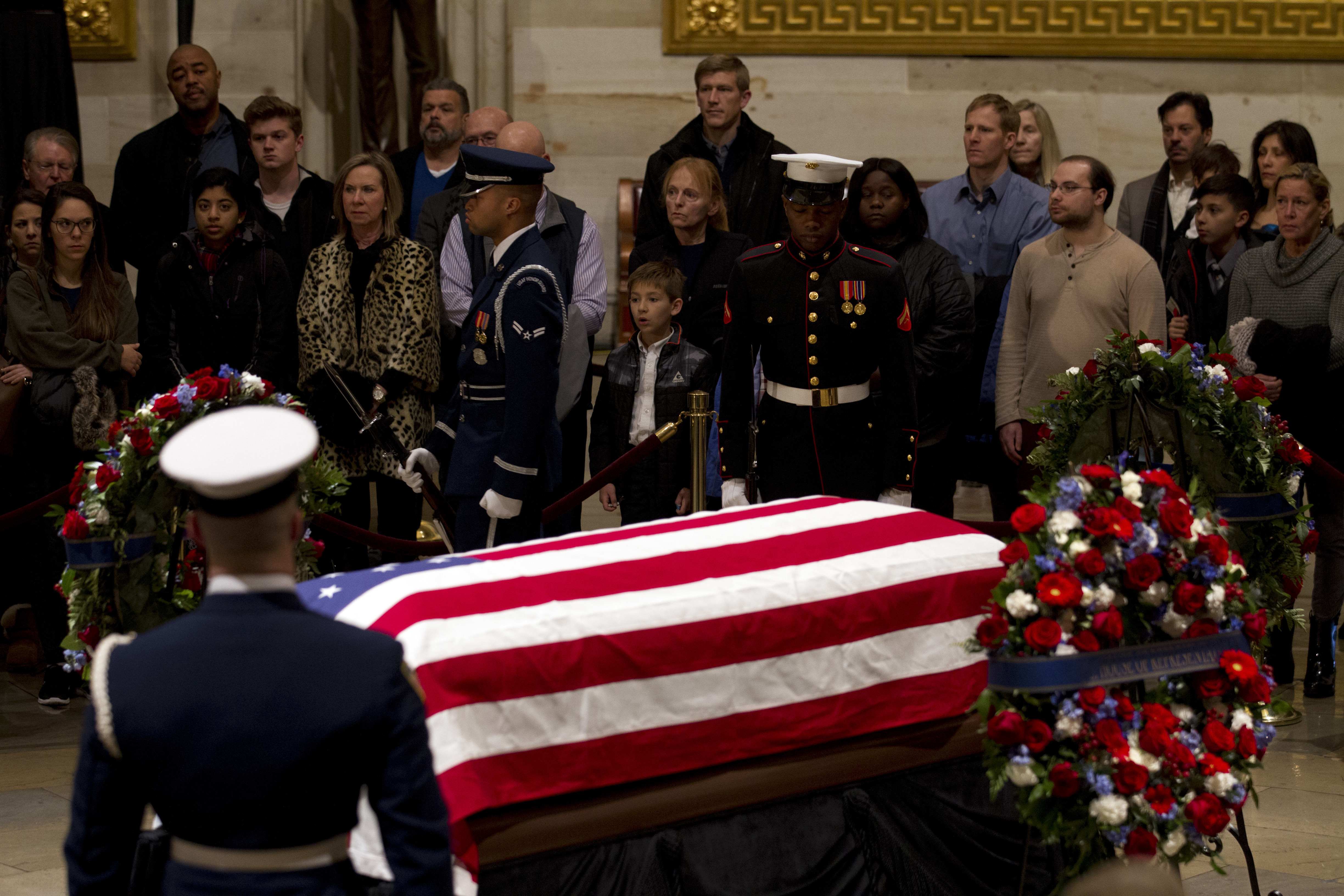 Visitors pay their respects at the flag-draped casket of former President George H.W. Bush, as he lies in state in the Capitol Rotunda in Washington, Wednesday, Dec. 5, 2018. (AP Photo/Jose Luis Magana)