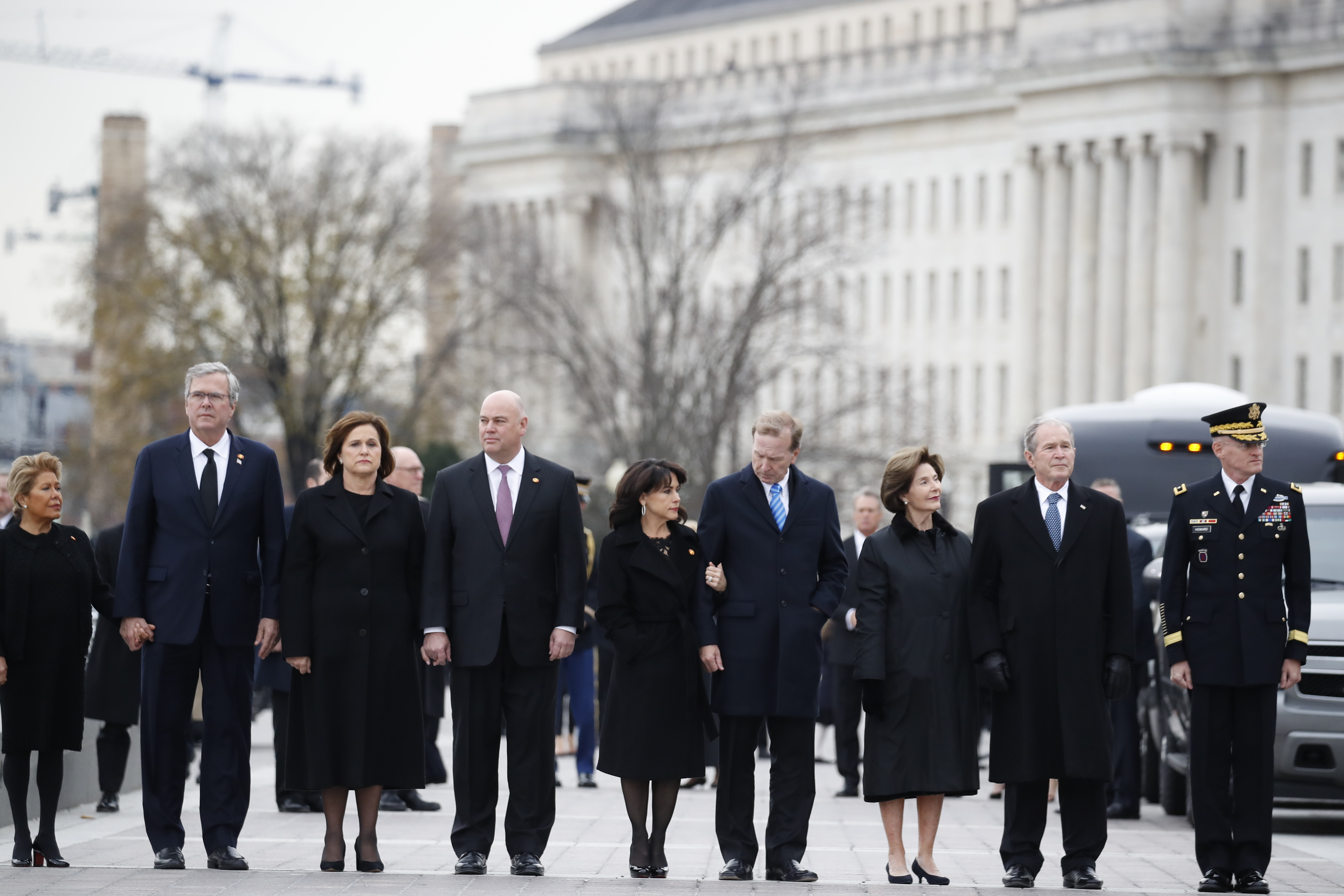 From right, former President George W. Bush, second from right, former first lady Laura Bush, Neil Bush, Maria Bush, Bobby Koch, Doro Koch, Jeb Bush and Columba Bush, stand just prior to the flag-draped casket of former President George H.W. Bush being carried by a joint services military honor guard from the U.S. Capitol, Wednesday, Dec. 5, 2018, in Washington. (AP Photo/Alex Brandon, Pool)