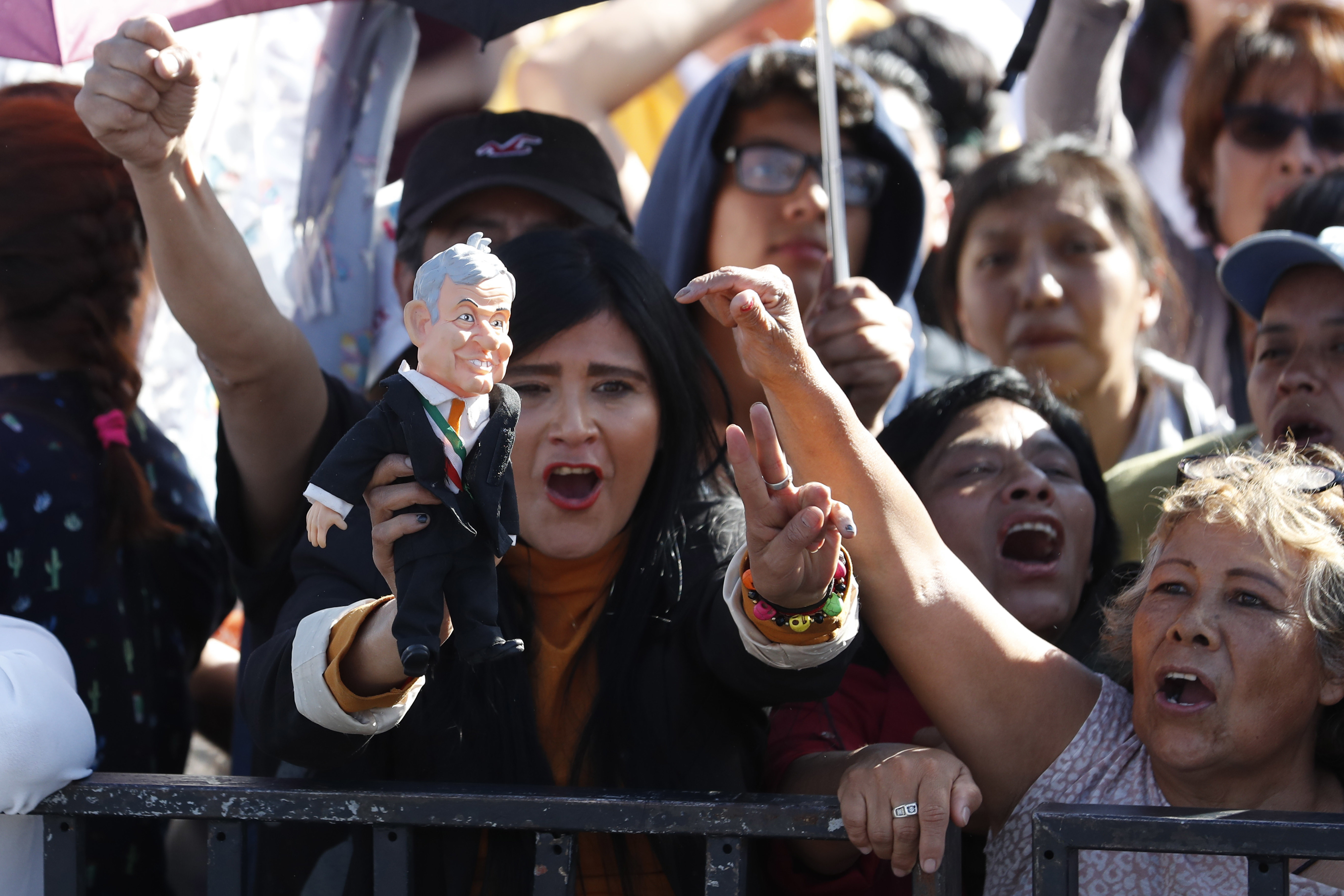 Celebrants get revved up as they gather in the Zocalo to see newly sworn-in President Andres Manuel Lopez Obrador, in Mexico City, Saturday, Dec. 1, 2018. Mexicans are getting more than just a new president Saturday. Lopez Obrador took the oath of office Saturday as Mexico's first leftist president in over 70 years, marking a turning point in one of the world's most radical experiments in opening markets and privatization. (AP Photo/Moises Castillo)