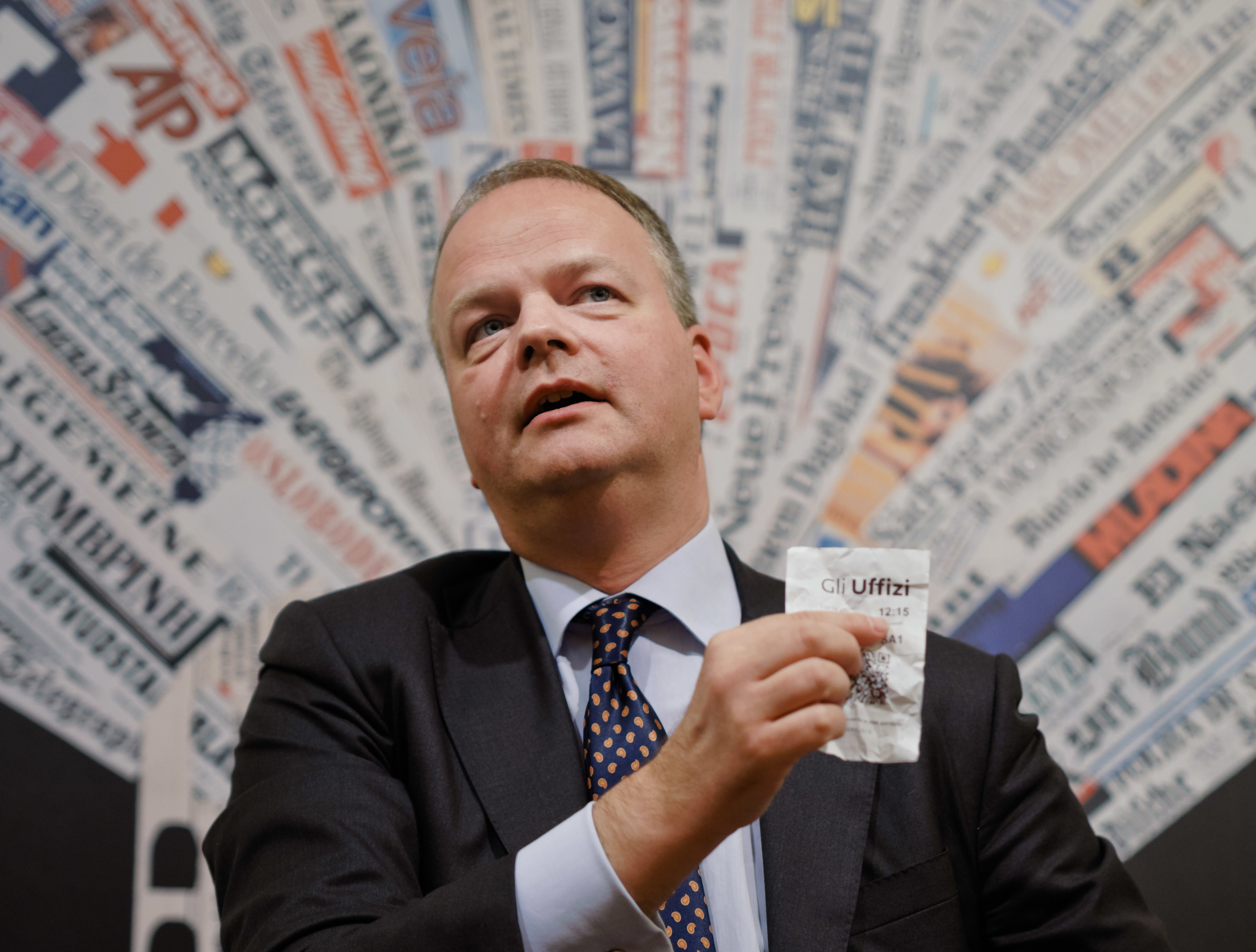 German art historian and director of the Uffizi galleries, Eike Schmidt, shows a ticket for the Uffizi Museum during a press conference at the Foreign Press Club in Rome, Wednesday, Dec. 5, 2018. The Uffizi Galleries in Florence aims to discourage visitor overcrowding and ticket scalpers. Schmidt says Italy's most-visited art museum is meeting with Italian privacy guarantors to devise ways to use purchasers' photos to thwart scalpers looking to resell tickets at exorbitant prices. (AP Photo/Domenico Stinellis)