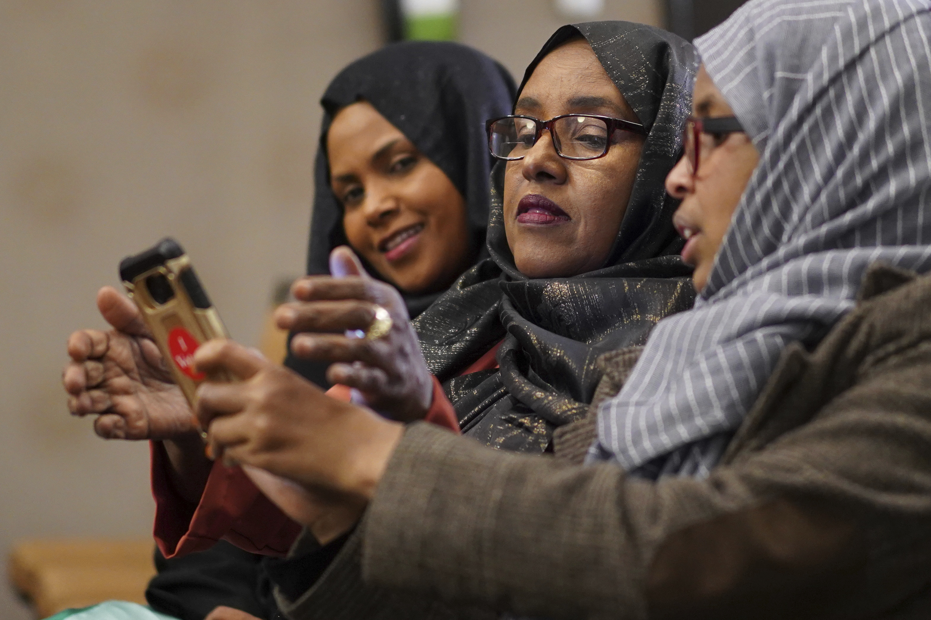Hibo Omar, Muhubo Shire and Kin Kyani watch results at Democratic congressional candidate Ilhan Omar's election night headquarters in Minneapolis on Tuesday, Nov. 6, 2018. State Rep. Ilhan Omar has won Minnesota's 5th District race to become the first Somali-American and one of the first Muslim women elected to Congress. (Mark Vancleave/Star Tribune via AP)