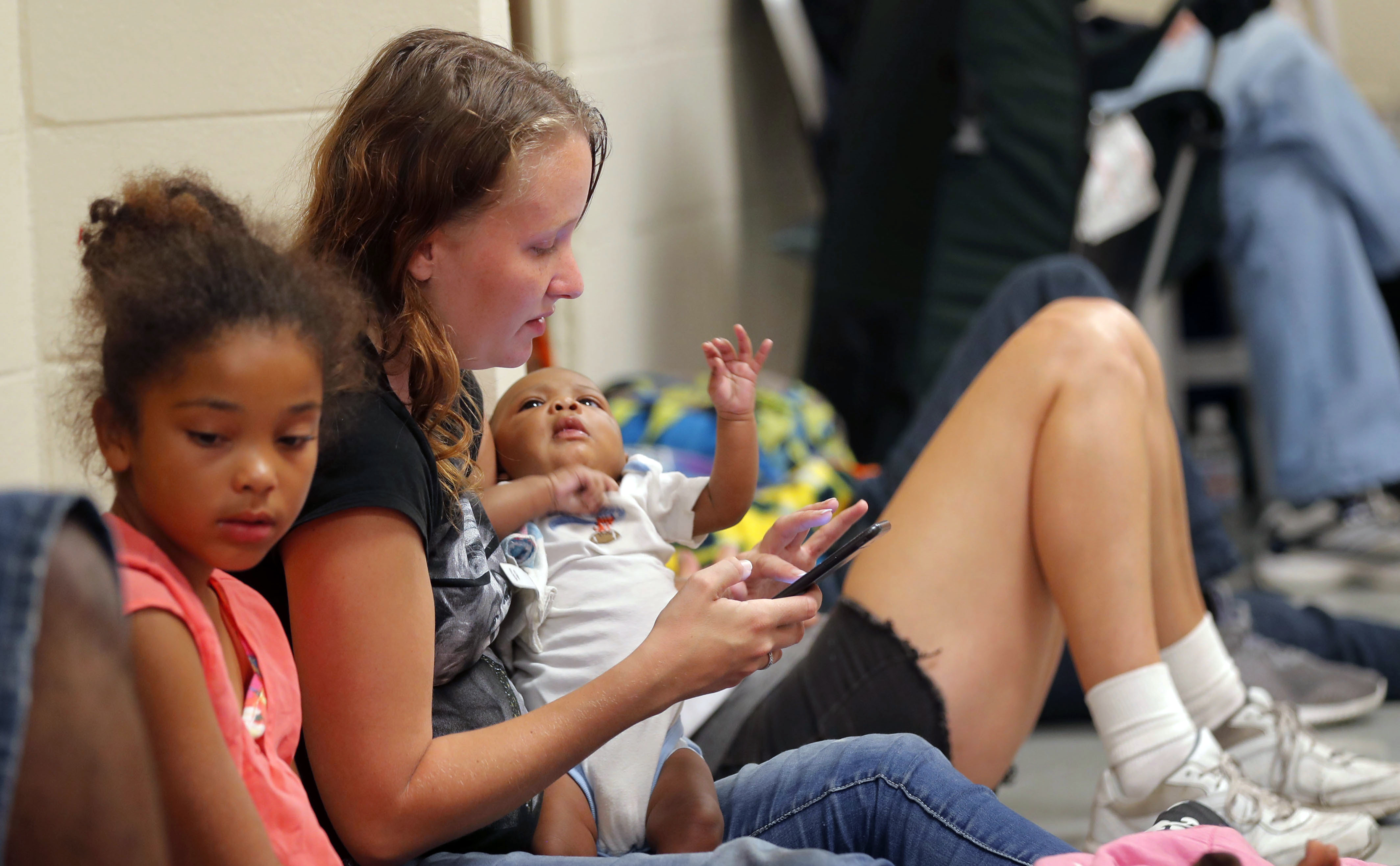 CORRECTS NAME OF HURRICANE TO MICHAEL FROM MATTHEW - Ashley Fillingim holds her godson Jerah'monie Anthony Bell, 2 months, at an evacuation shelter set up at Rutherford High School, in Panama City Beach, Fla., in advance of Hurricane Michael, which is expected to make landfall, Wednesday, Oct. 10, 2018. (AP Photo/Gerald Herbert)