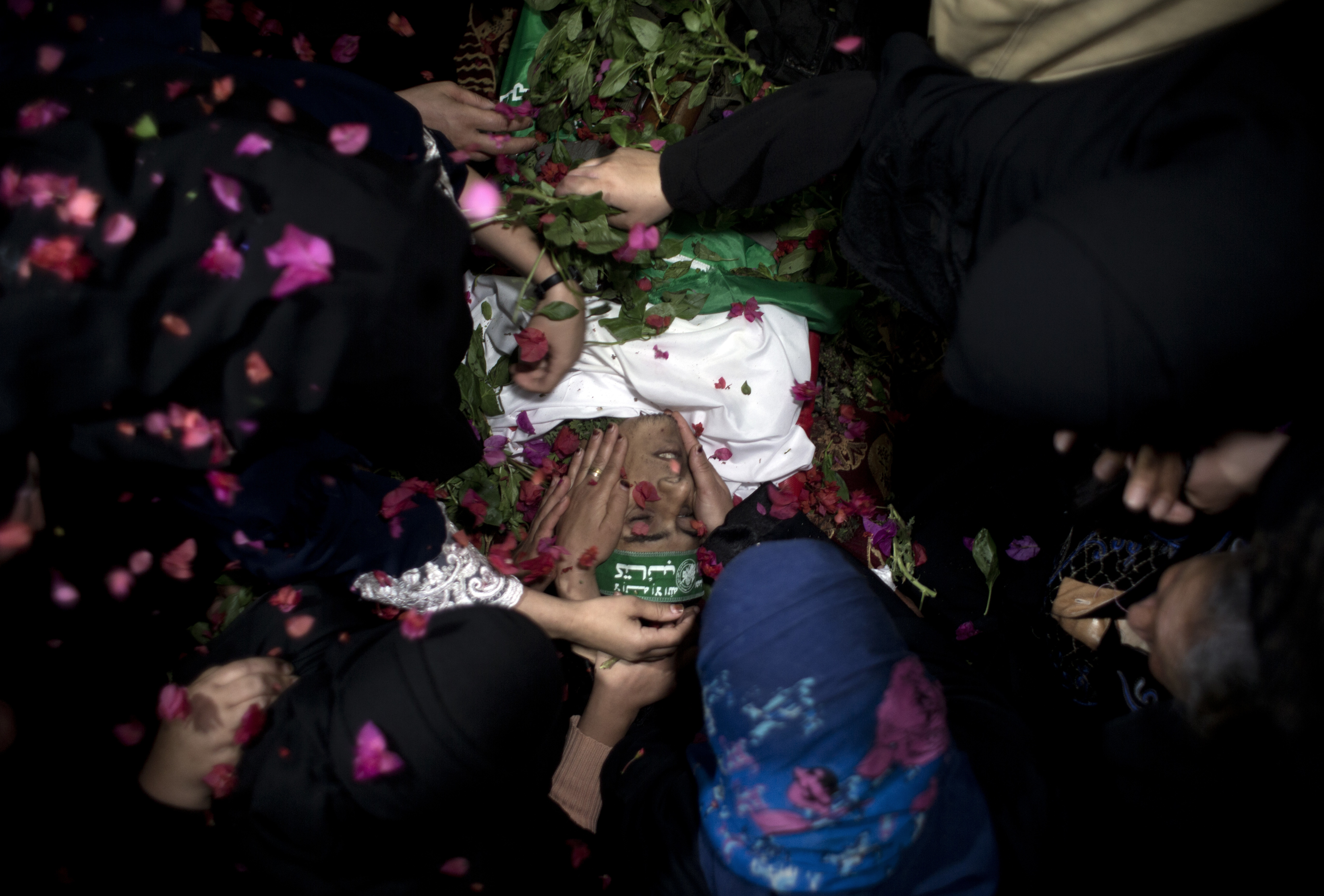 Relatives of Ahmed Abu Lebdeh, 22, who was killed by Israeli troops during Friday's protest at the Gaza Strip's border with Israel, mourn over his body into the family home during his funeral in town of Khan Younis, southern Gaza Strip, Saturday, Oct. 27, 2018. (AP Photo/Khalil Hamra)