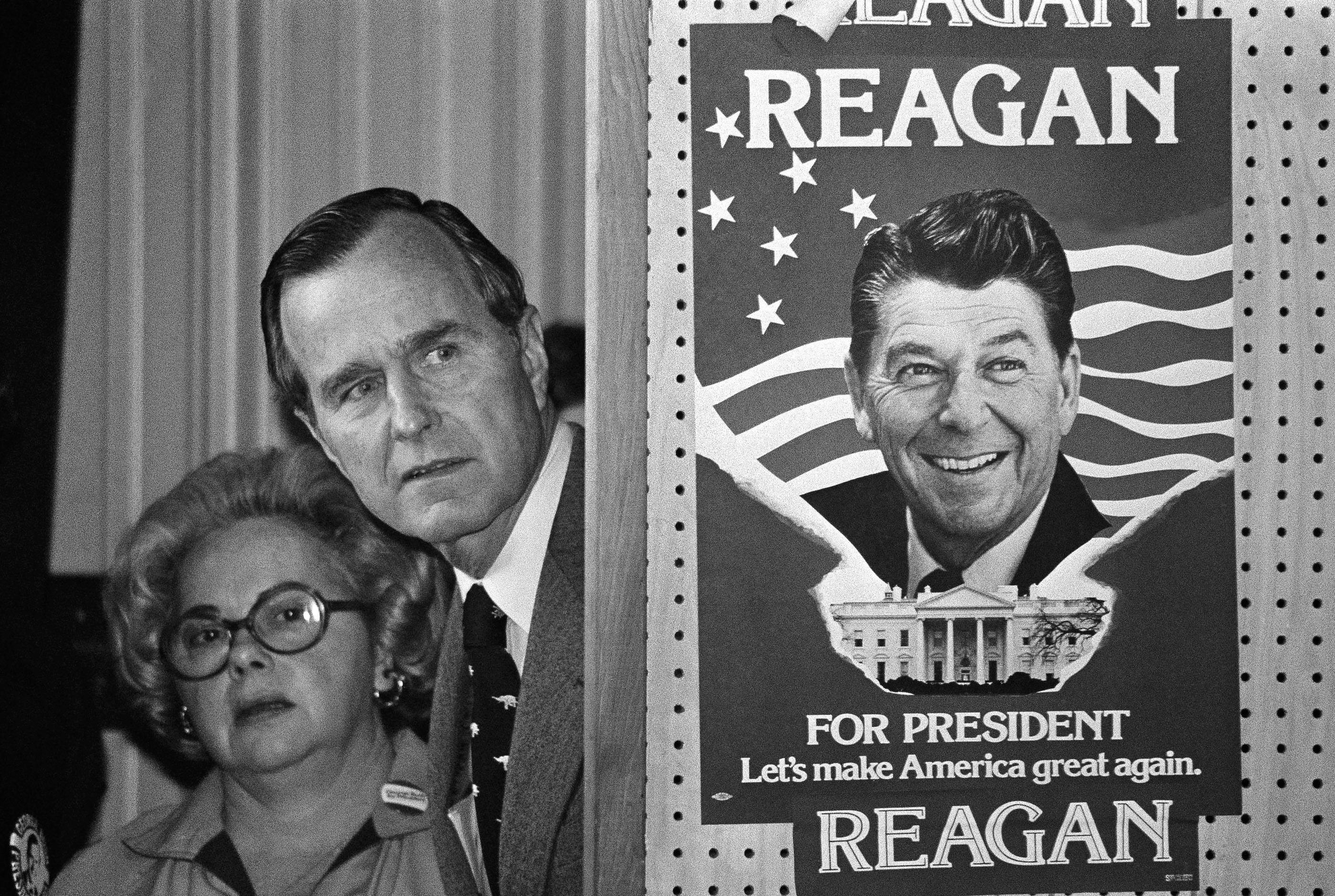 In this March 4, 1980 photo, George H.W. Bush and an unidentified woman peek around a partition with a poster of Ronald Reagan, one of his opponents for the Republican party presidential nomination, before he speaks in Columbia, SC. (AP Photo, File)
