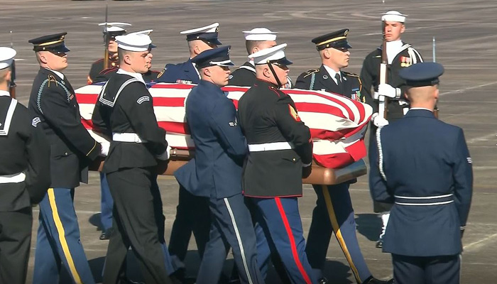 Members of the military carry the casket of President George H.W. Bush to the plane for transport to Washington, DC on Monday. The former president will lie in state at the Capital.