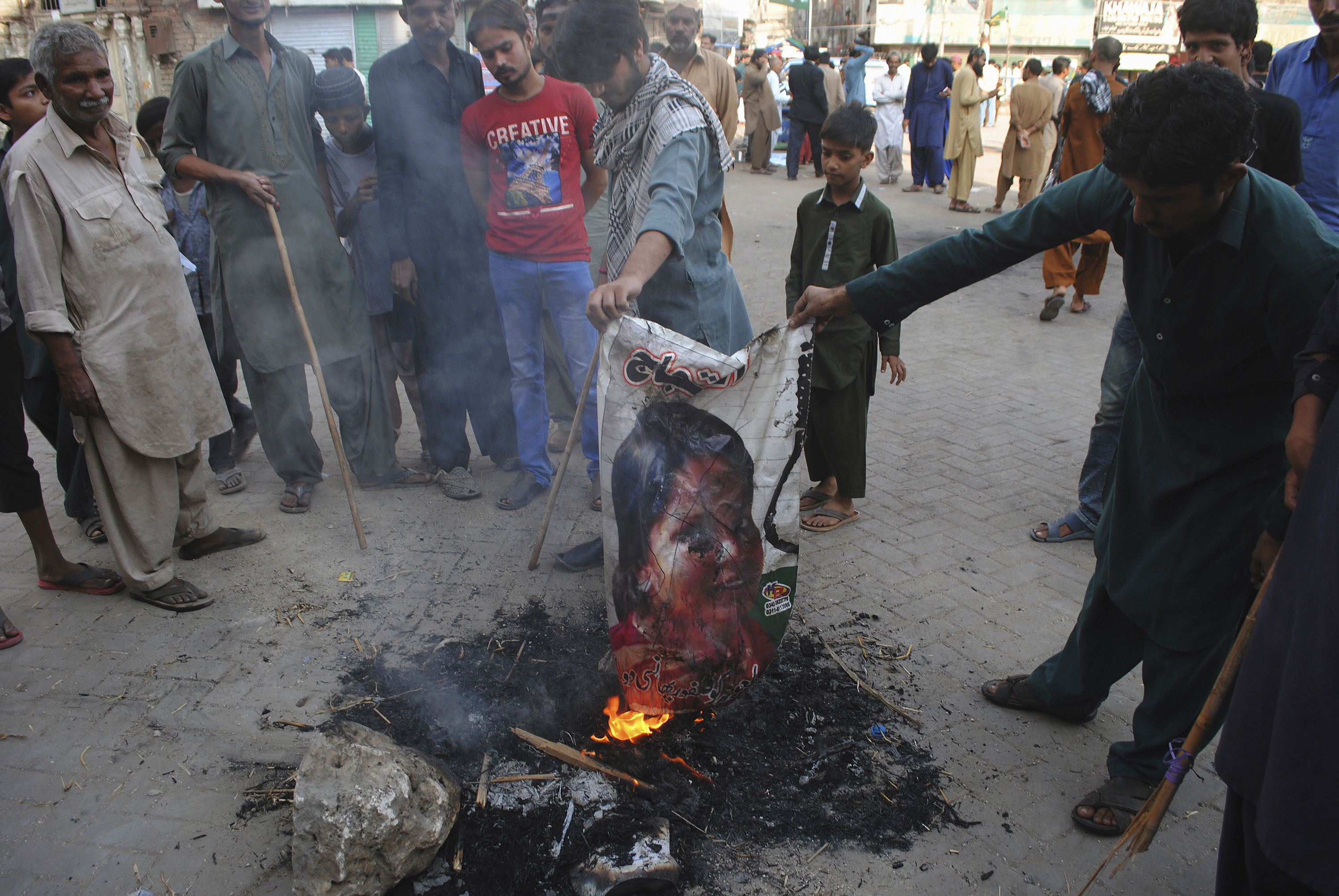 FILE - In this Nov. 1, 2018, file photo, Pakistani protesters burn a poster image of Christian woman Aasia Bibi, in Hyderabad, Pakistan. The Christian woman acquitted after eight years on death row for blasphemy was released but her whereabouts in Islamabad on Thursday, Nov. 8 remained a closely guarded secret in the wake of demands by radical Islamists that she be publicly executed. (AP Photo/Pervez Masih, File)