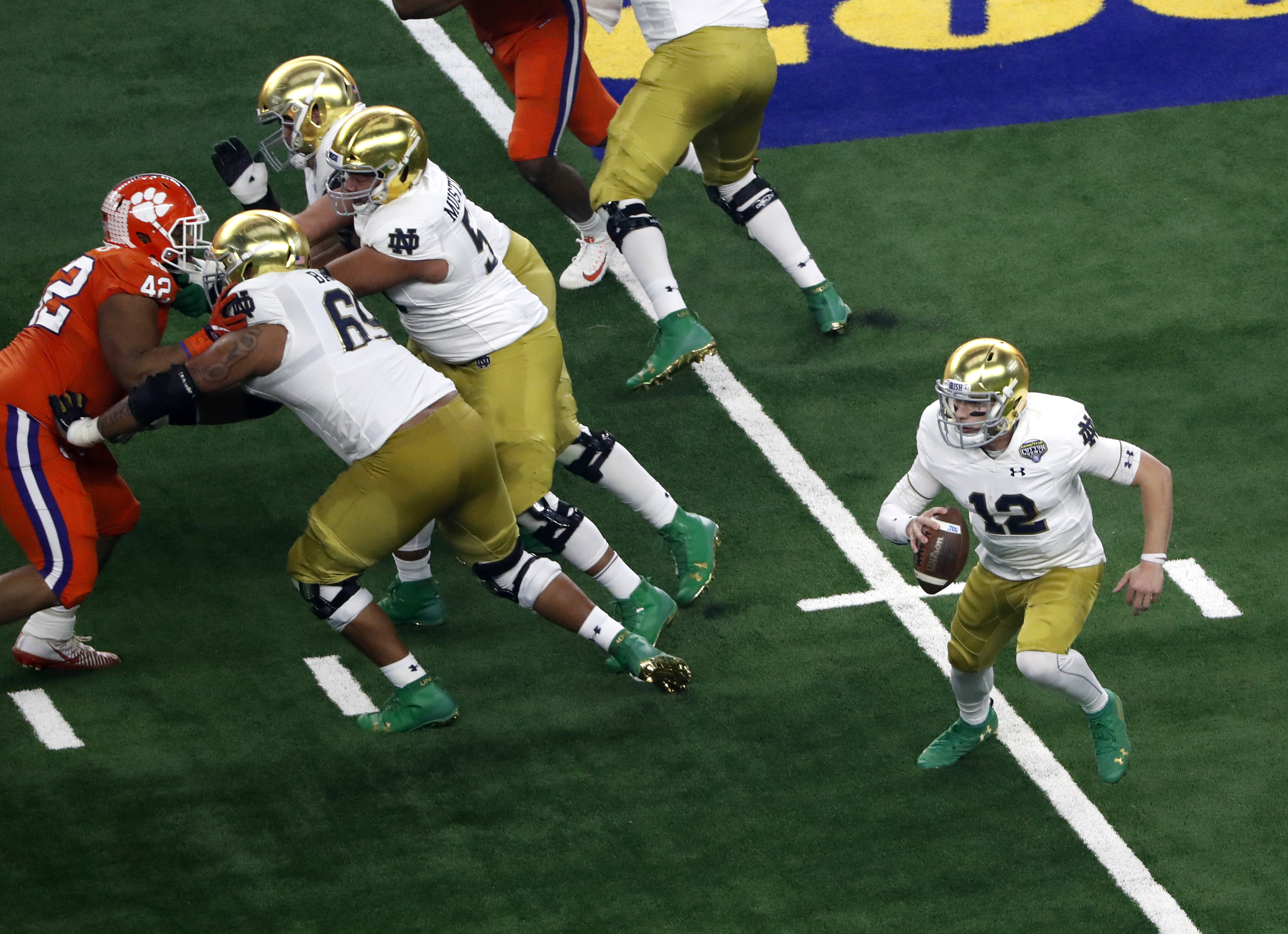 Notre Dame quarterback Ian Book (12) scrambles out of the pocket for a gain in the first half of the NCAA Cotton Bowl semi-final playoff football game against Clemson on Saturday, Dec. 29, 2018, in Arlington, Texas. (AP Photo/Roger Steinman)