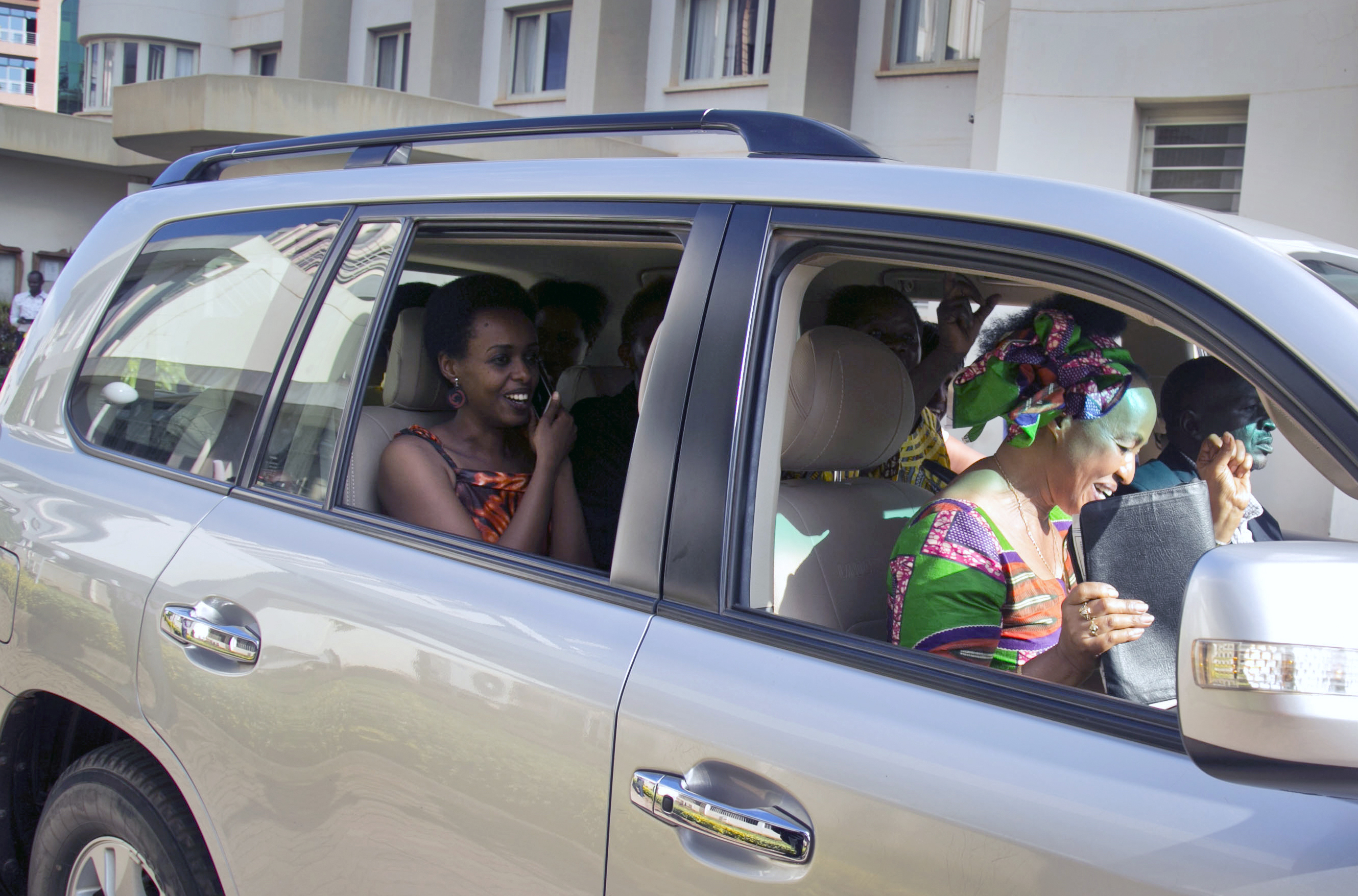 Diane Rwigara, 37, the country's most prominent opposition figure, left, smiles accompanied by her mother, Adeline, 59, right, as they drive off after Diane was acquitted of charges related to her election challenge of President Paul Kagame, at the high court in Kigali, Rwanda Thursday, Dec. 6, 2018. Rwanda's high court on Thursday acquitted Rwigara of all charges, as judges said the prosecution failed to provide proof of insurrection and forgery. (AP Photo)