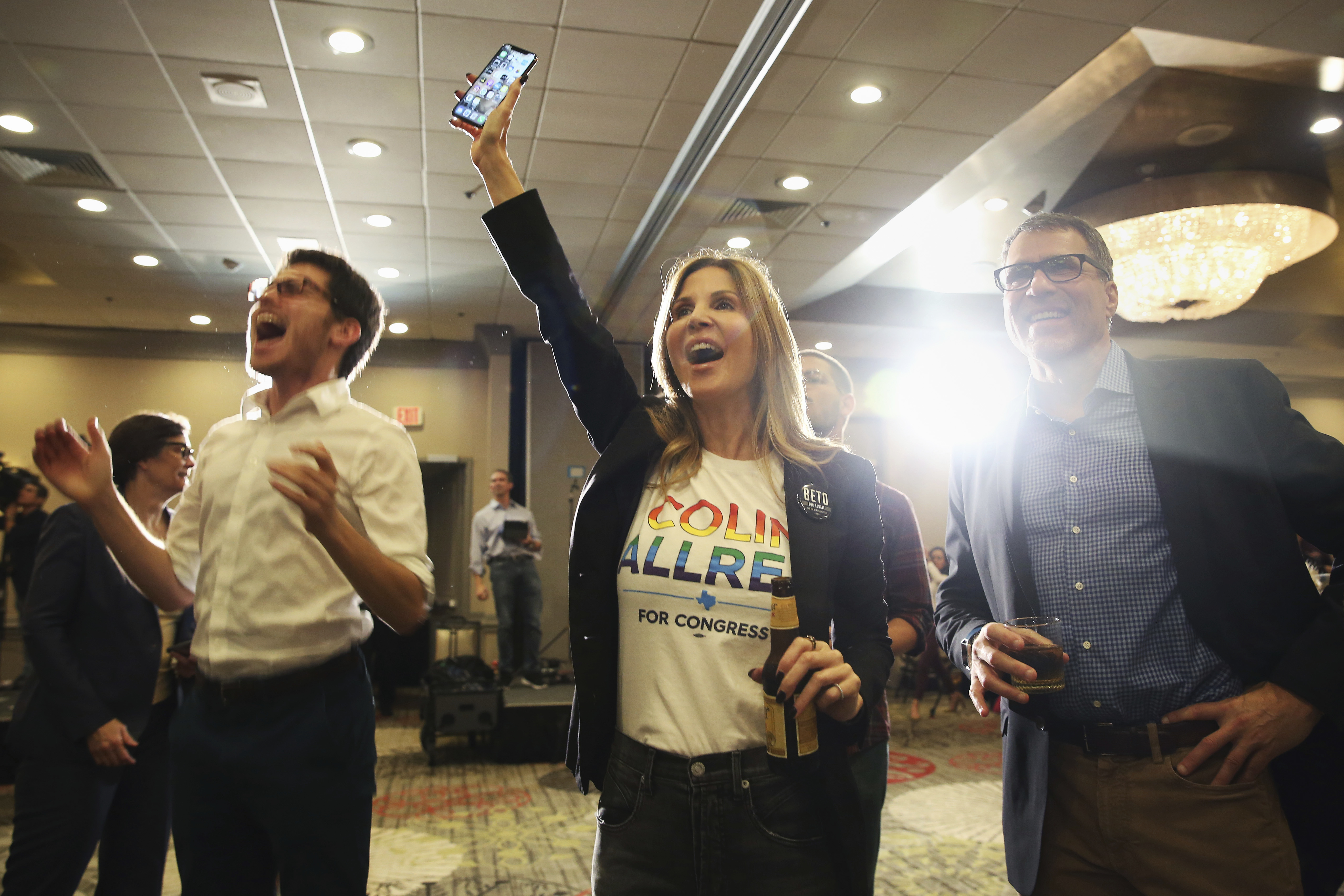David Rosen, from left, Jennifer Karol and her husband Tom Karol react to an update on the 32nd Texas congressional race during an election night party for Democratic candidate Colin Allred at the Magnolia Hotel Dallas Park Cities in Dallas, Tuesday, Nov. 6, 2018. Allred defeated GOP incumbent Republican Pete Sessions for the Texas 32nd U.S. congressional house district. (AP Photo/Andy Jacobsohn)