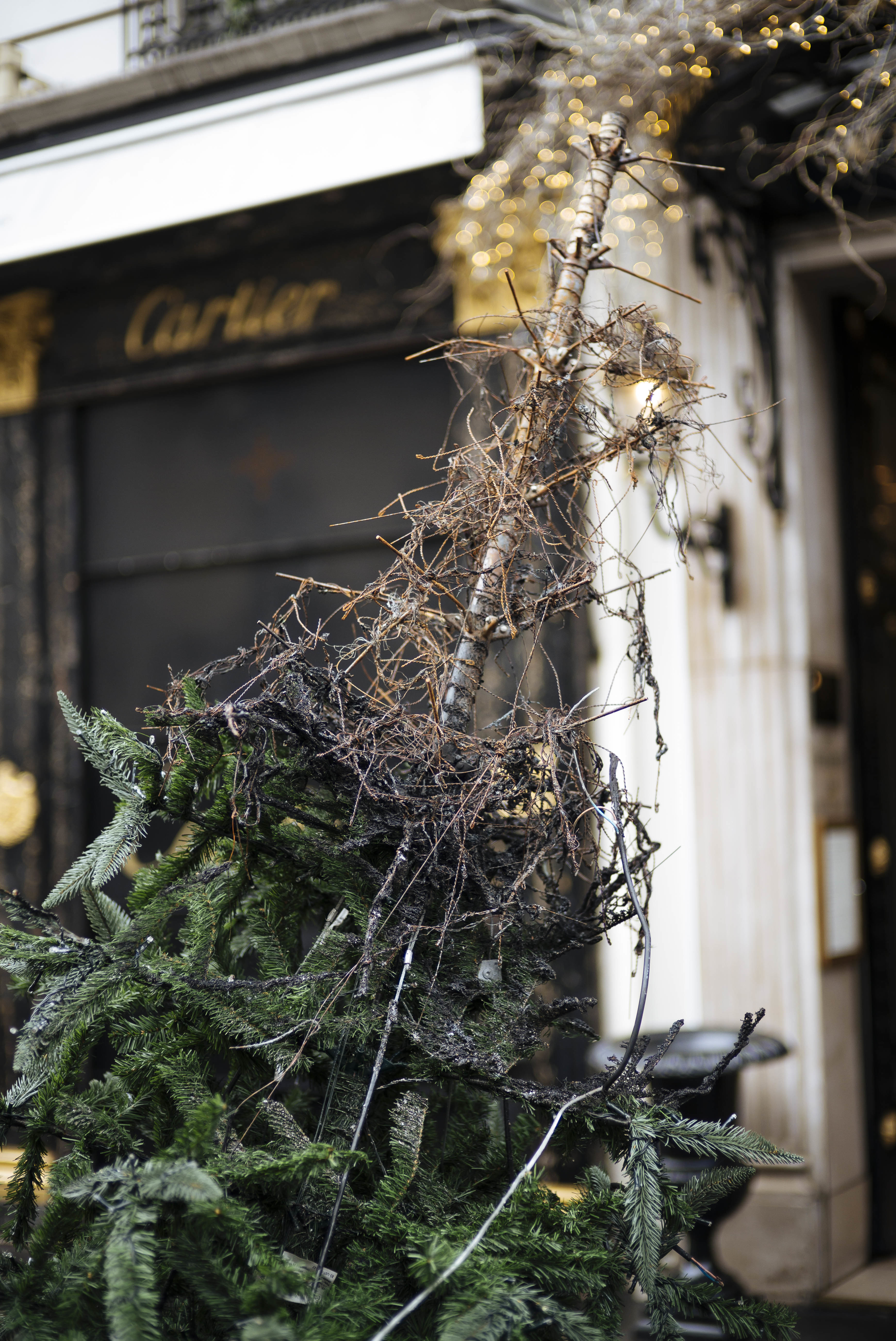 A half burned Christmas tree is seen on the Vendome plaza in Paris, Sunday, Dec. 2, 2018. A protest against rising taxes and the high cost of living turned into a riot in the French capital Saturday, as activists caused widespread damage and tagged the Arc de Triomphe with multi-colored graffiti during clashes with police. (AP Photo/Kamil Zihnioglu)