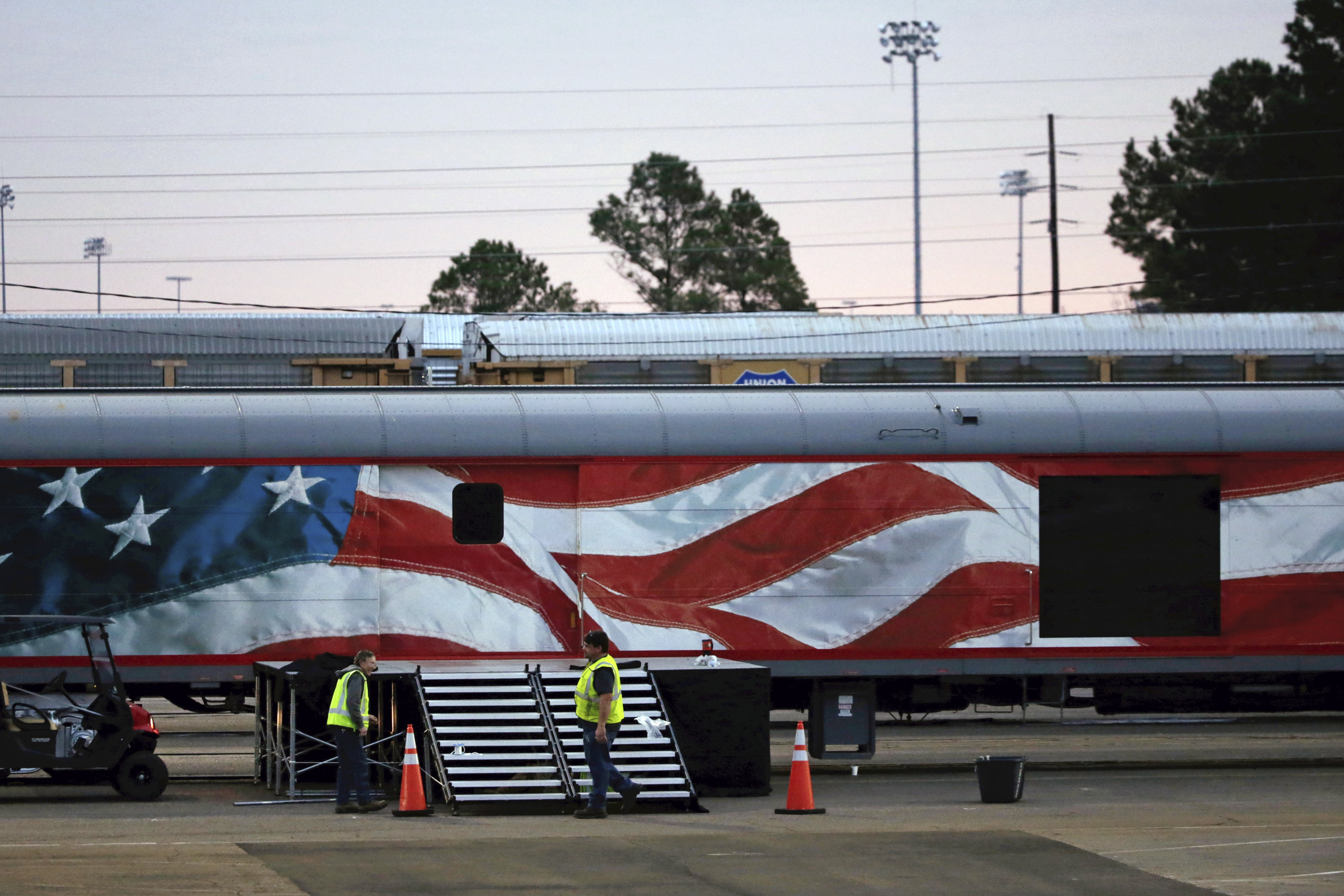 Workers prepare for a departure ceremony of the casket of former President George H.W. Bush at Union Pacific Westfield auto facility Thursday, Dec. 6, 2018, in Spring. The Plexiglass door, right, will allow the public to see Bush's casket as it hauled on the route. (AP Photo/Kiichiro Sato)