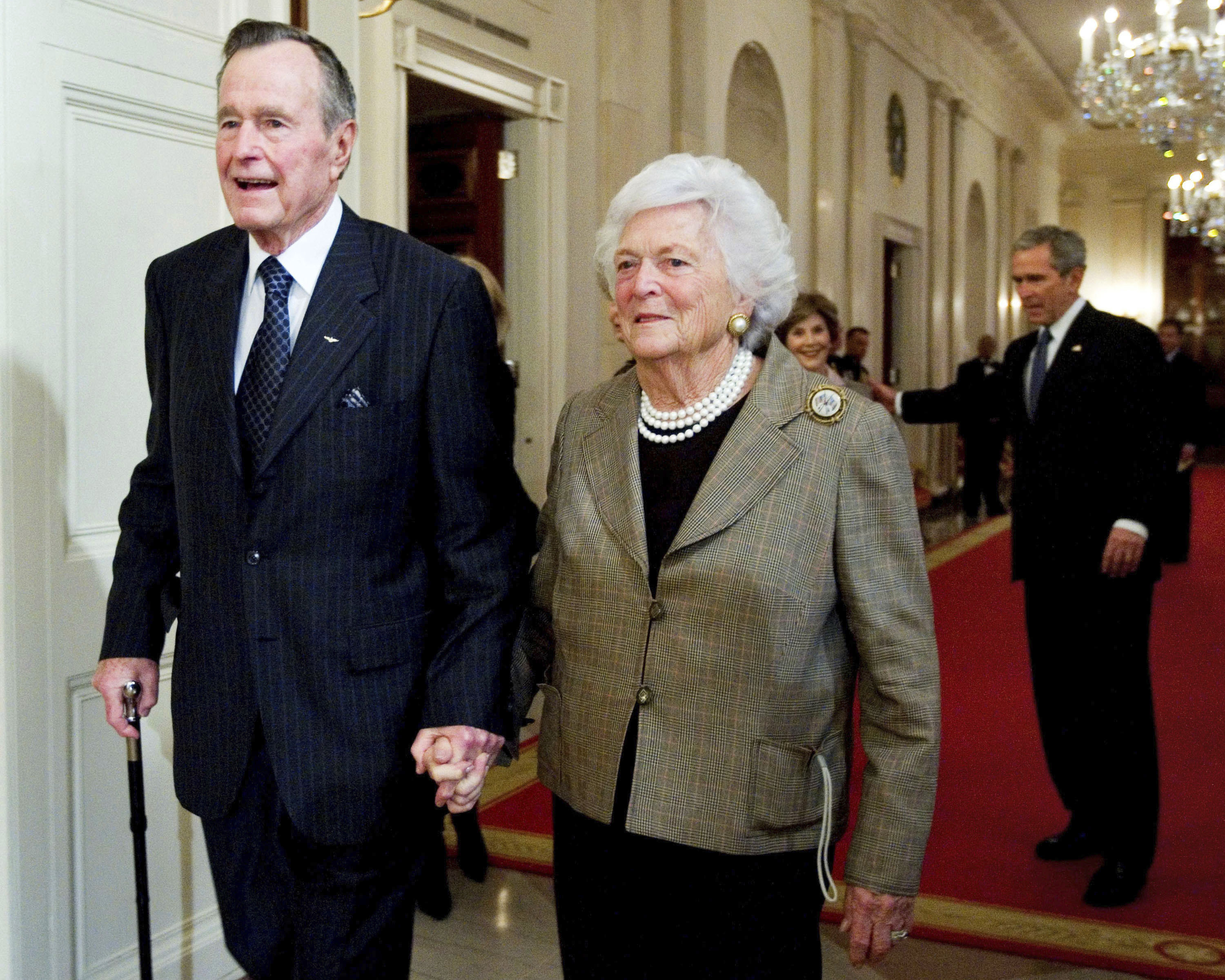 In this Jan. 7, 2009, photo, former President George H. W. Bush, left, walks with his wife, former first lady Barbara Bush, followed by their son, President George W. Bush, and his wife first lady Laura Bush, to a reception in honor of the Points of Light Institute, in the East Room at the White House in Washington. (AP Photo/Manuel Balce Ceneta, File)