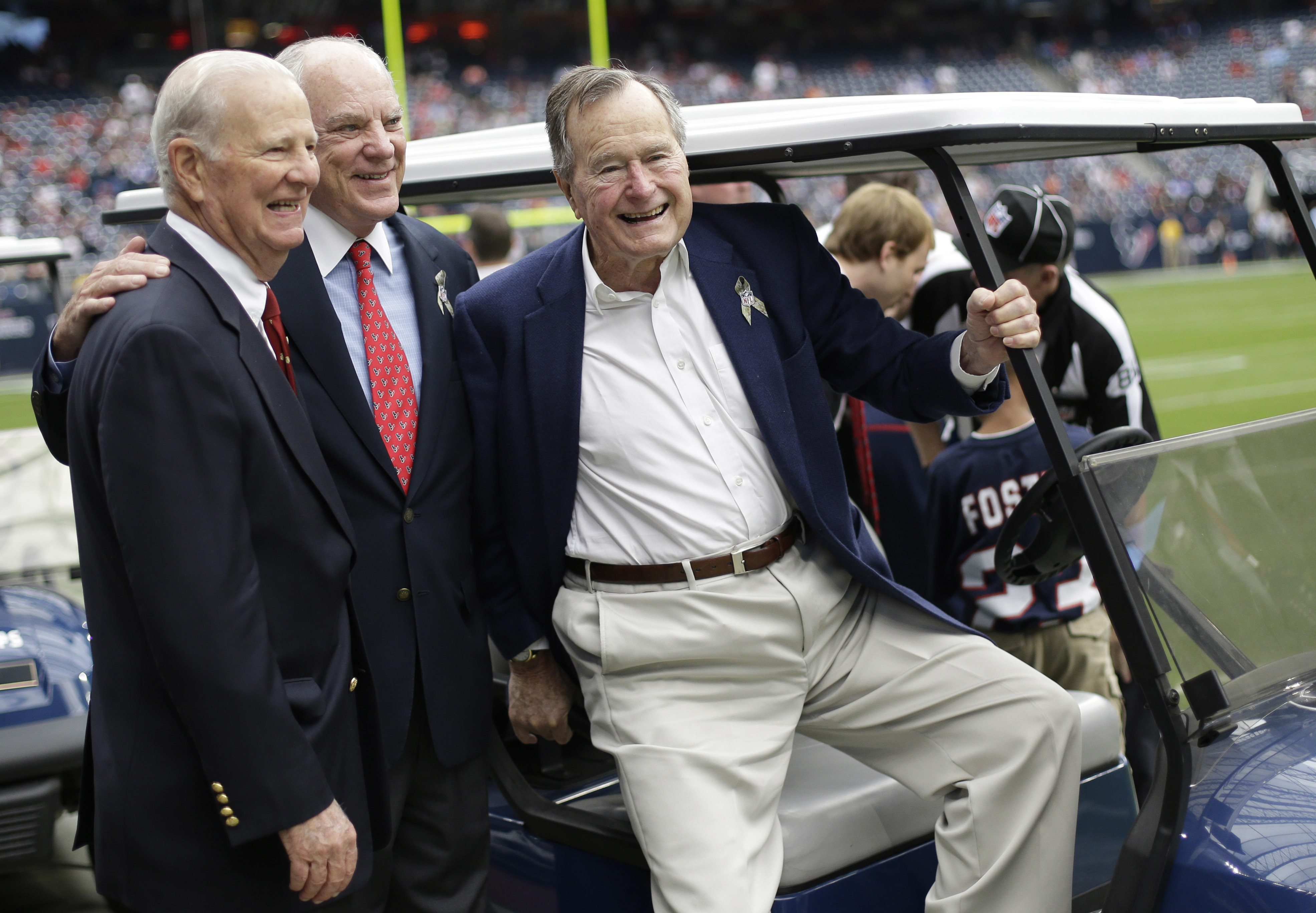 "In this Nov. 4, 2012, photo, former President George H. W. Bush, right, former Secretary of State James Baker, left, and Houston Texans owner Bob McNair pose together before an NFL football game against the Buffalo Bills in Houston. Bush didn't lose his sense of humor even as he was letting go of life. Bush's longtime friend James A. Baker III tells the story of how his wife, Susan, put a hand on the former president's forehead and told him he's loved very much. At which point Baker says Bush ""cocked"" open an eye and quipped, ""Well, you better hurry."" Bush died Friday at age 94. (AP Photo/Eric Gay)"