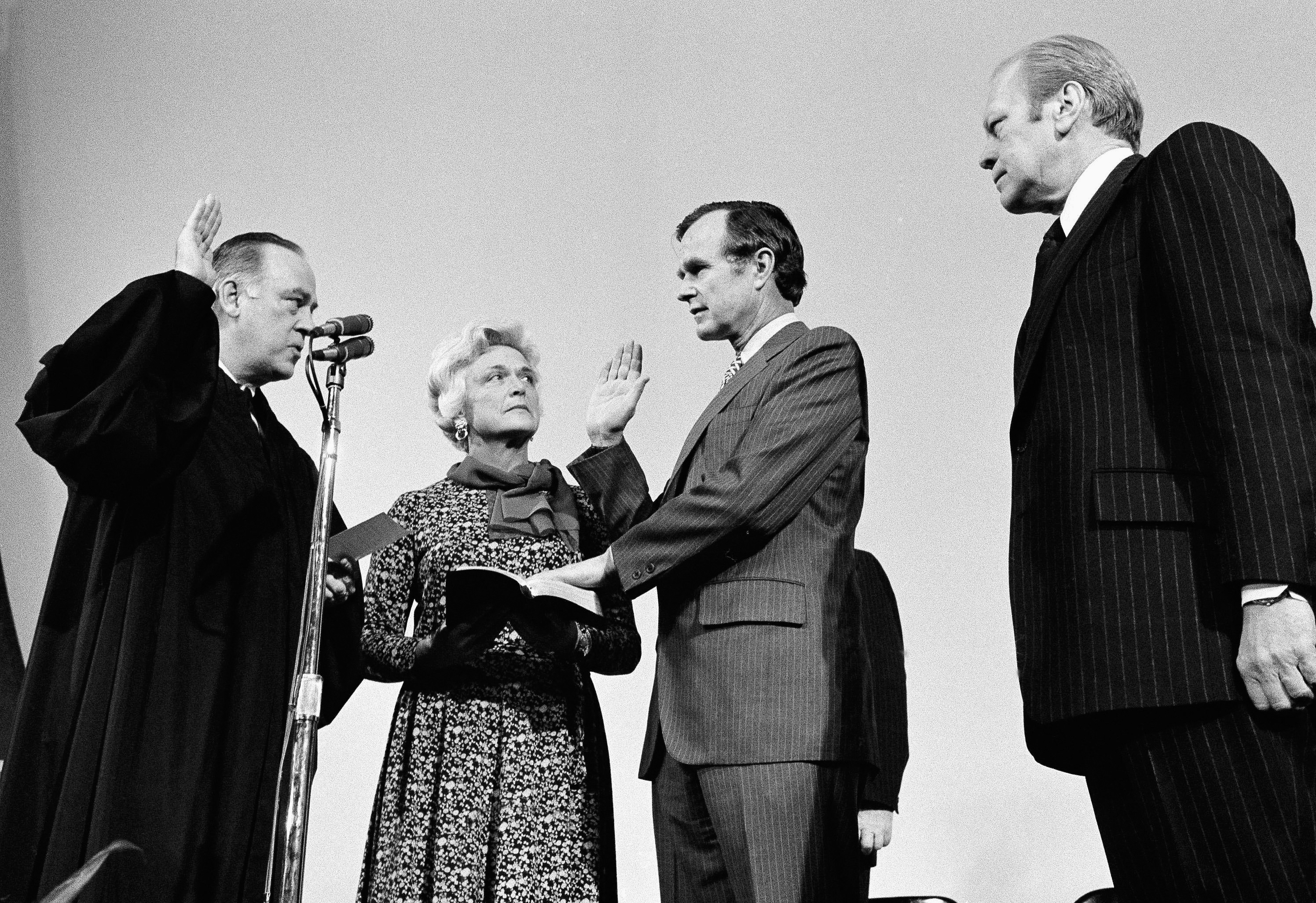 George H.W. Bush, center, is sworn in as director of the Central Intelligence Agency by Supreme Court Associate Justice Potter Stewart, left, as Barbara Bush and President Gerald Ford, right, look on at CIA headquarters in Langley, Va. He served in this role beginning in 1976 for about a year. (AP Photo/File)