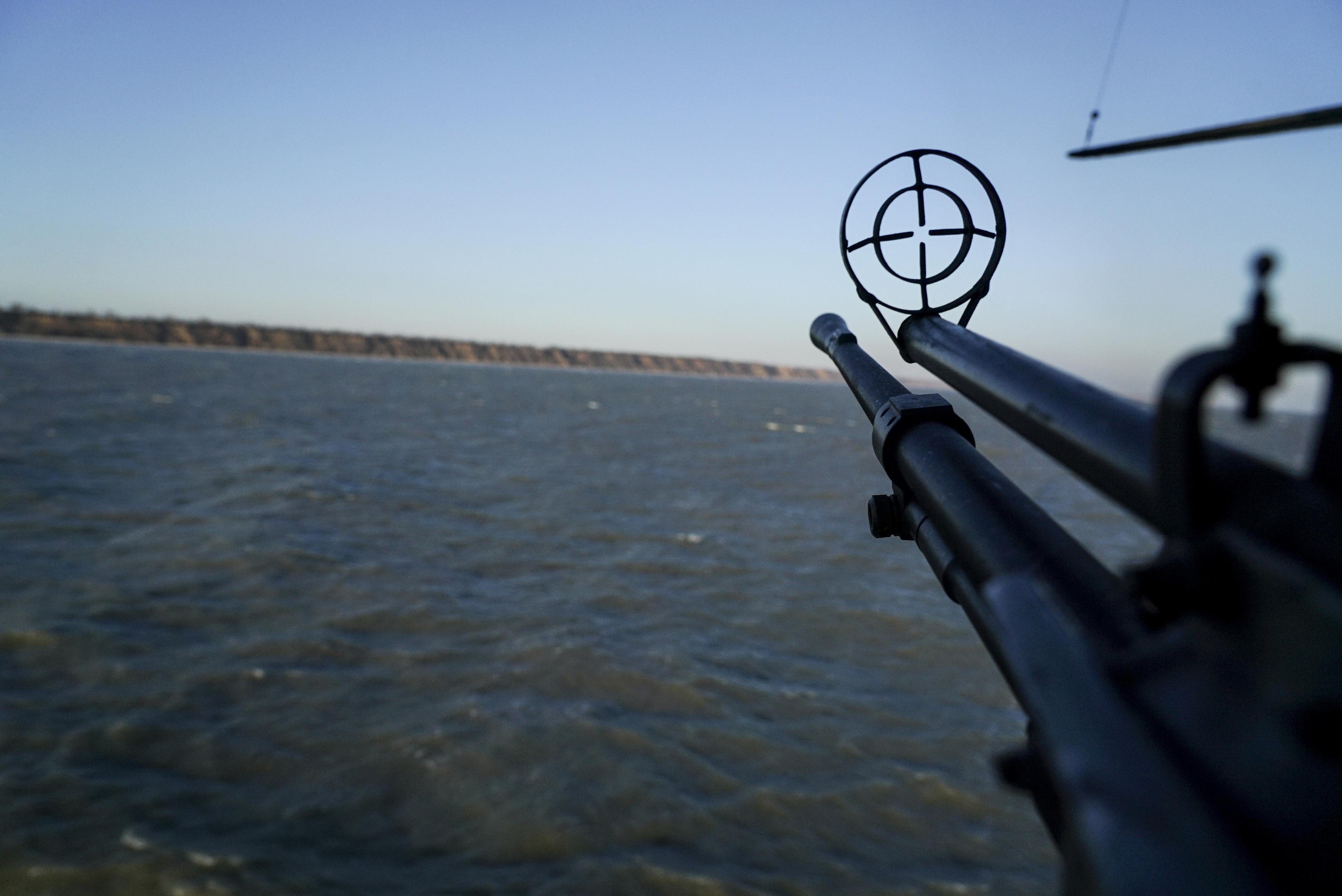 A helicopter's machine gun is turned toward the sea shore during patrol near Urzuf, south coast of Azov sea, eastern Ukraine, Thursday, Nov. 29, 2018. Ukraine put its military forces on high combat alert and announced martial law this week after Russian border guards fired on and seized three Ukrainian ships in the Black Sea. (AP Photo/Evgeniy Maloletka)