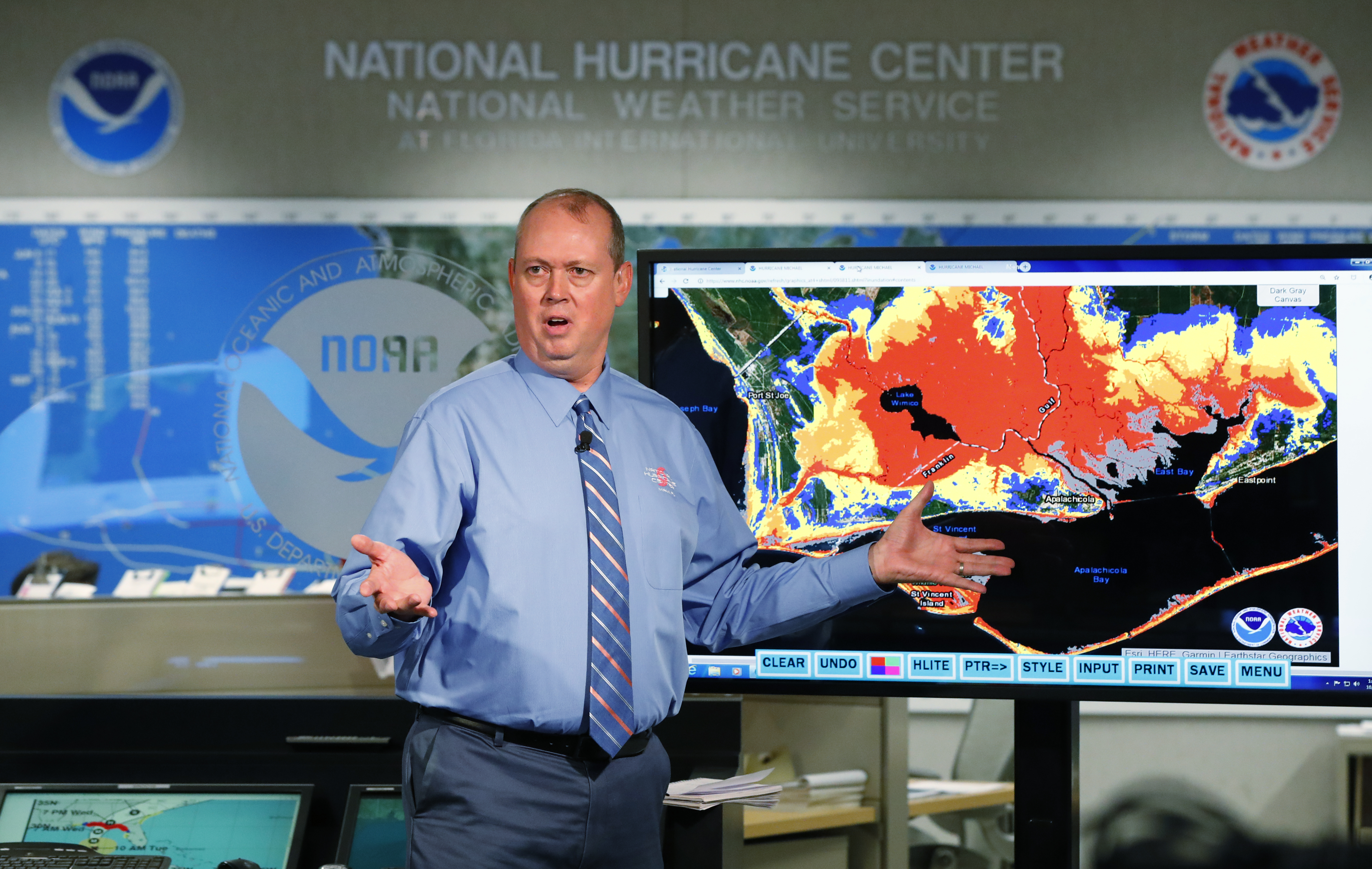 National Hurricane Center director Ken Graham, gestures as he talks about storm surge during a televised update on the status of Hurricane Michael, Tuesday, Oct. 9, 2018, at the Hurricane Center in Miami. At least 120,000 people along the Florida Panhandle were ordered to clear out Tuesday as Hurricane Michael rapidly picked up steam in the Gulf of Mexico and closed in with winds of 110 mph (175 kph) and a potential storm surge of 12 feet (3.7 meters). (AP Photo/Wilfredo Lee)
