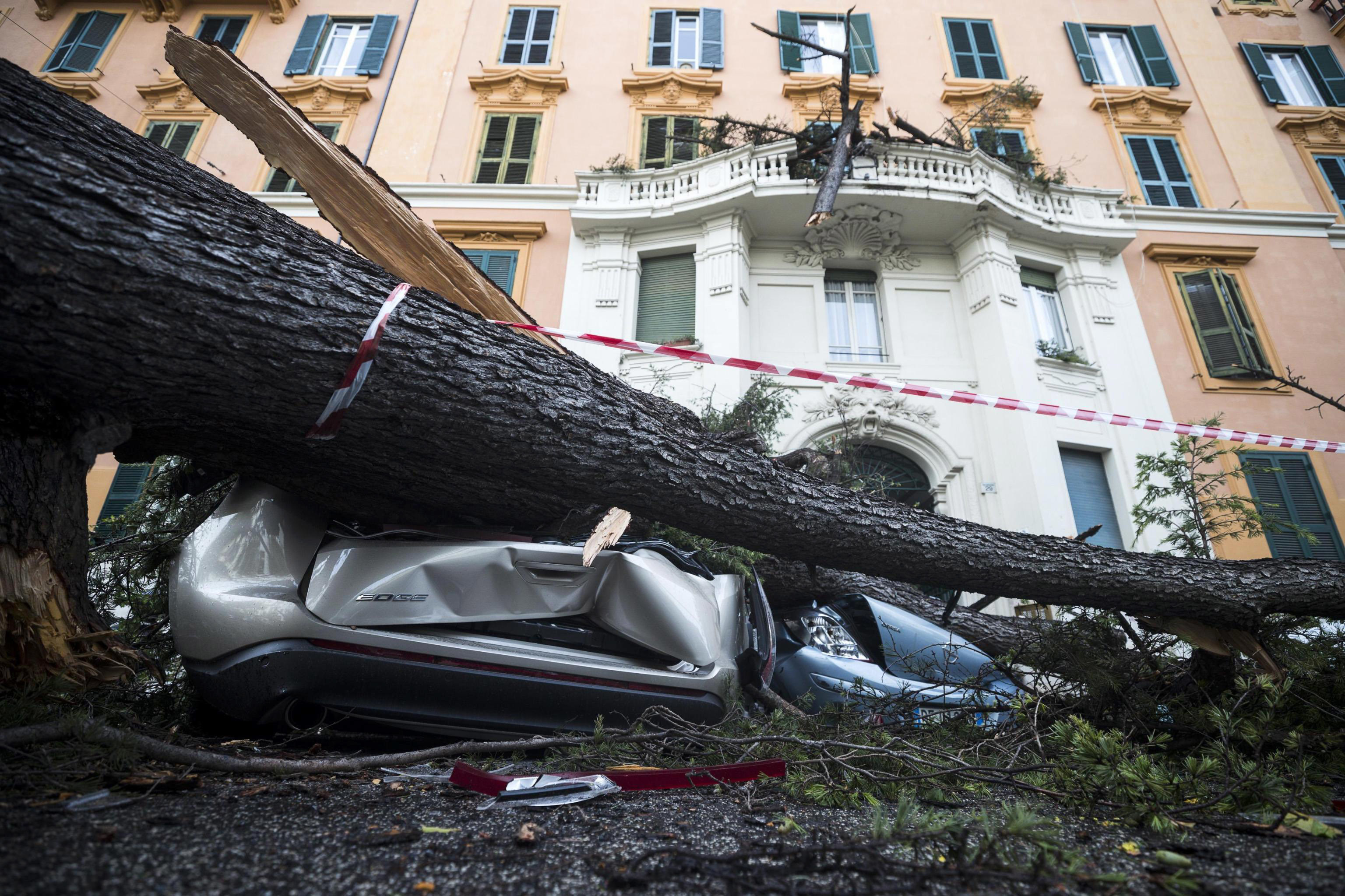 A car is crushed under a fallen tree and a balcony is partially destroyed by its branches after it was torn down by heavy winds, in Rome, Monday, Oct. 29, 2018. The national Civil Protection Agency has issued red and orange alerts -- meaning possible
