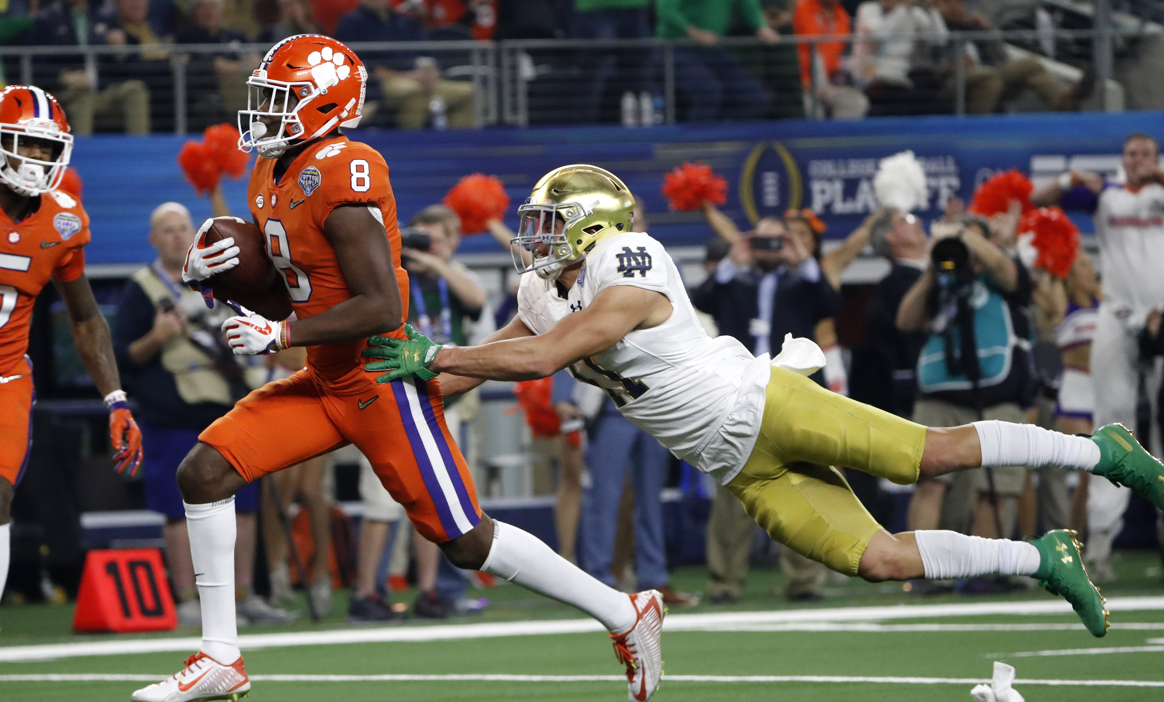 Clemson wide receiver Justyn Ross (8) escapes a tackle attempt by Notre Dame safety Alohi Gilman, right, as Ross reaches the end zone for a touchdown in the first half of the NCAA Cotton Bowl semi-final playoff football game, Saturday, Dec. 29, 2018, in Arlington, Texas. (AP Photo/Roger Steinman)