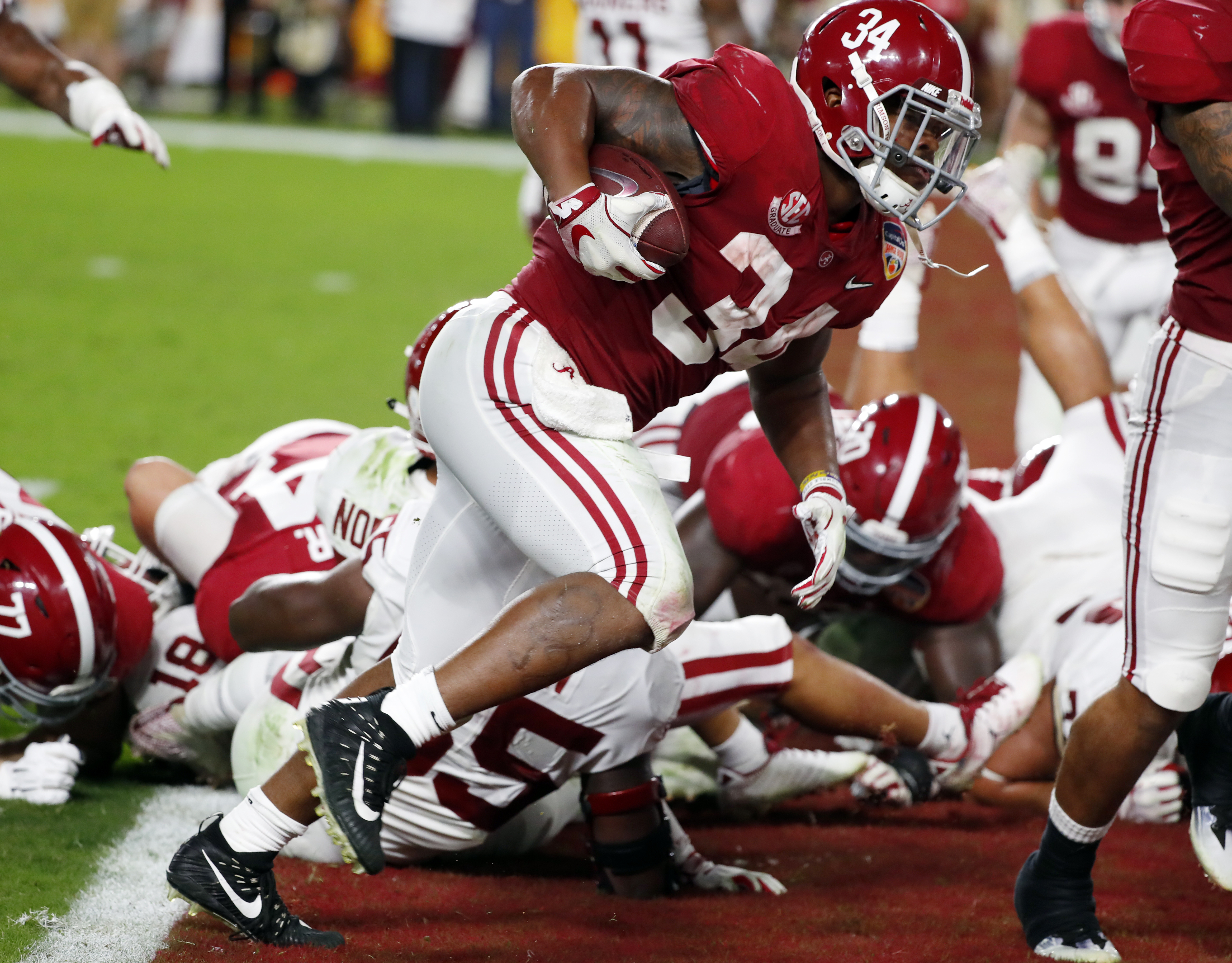 Alabama running back Damien Harris (34) scores a touchdown, during the first half of the Orange Bowl NCAA college football game against Oklahoma, Saturday, Dec. 29, 2018, in Miami Gardens, Fla. (AP Photo/Wilfredo Lee)