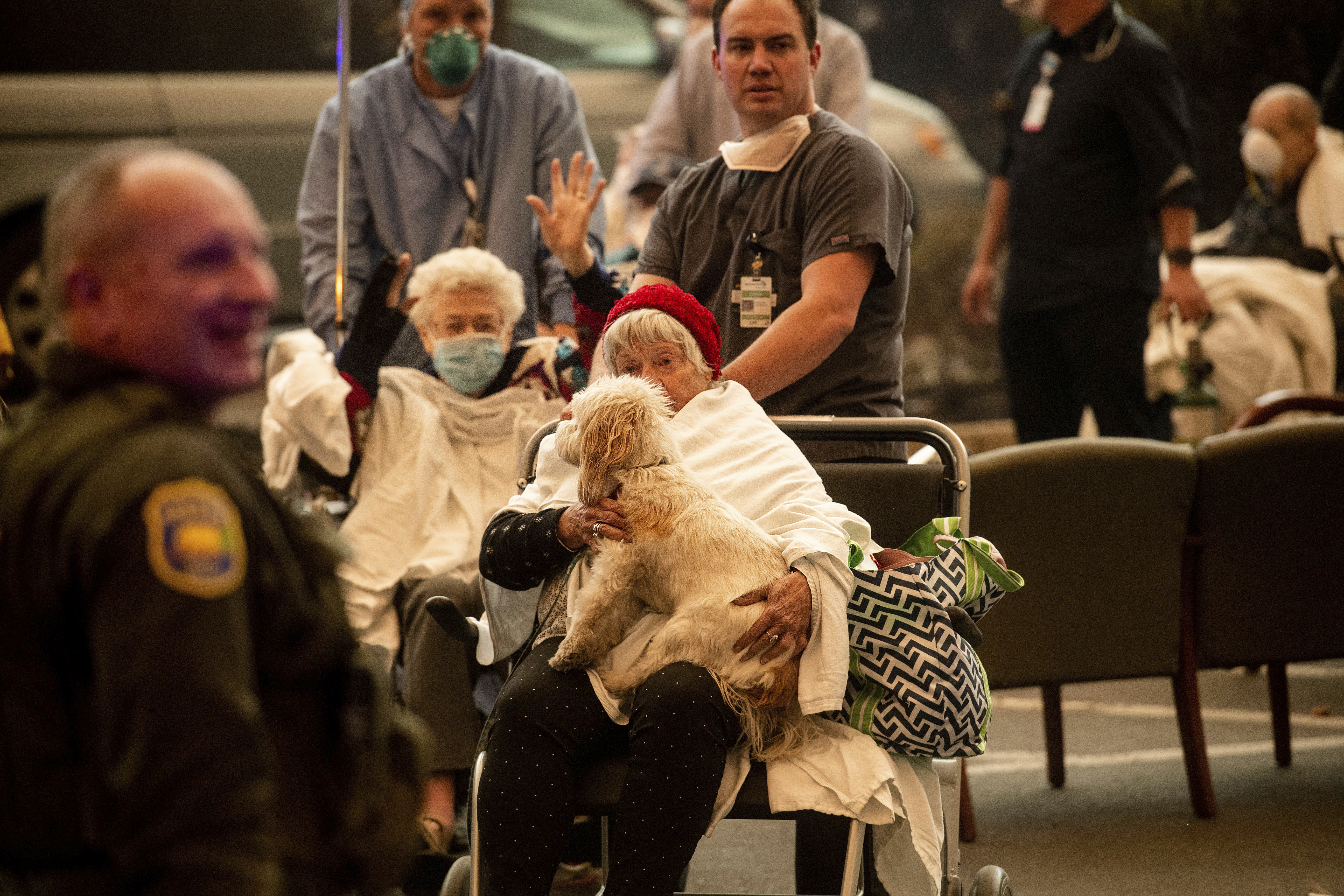 Medical personnel evacuate patients as the Feather River Hospital burns while the Camp Fire rages through Paradise, Calif., on Thursday, Nov. 8, 2018. Tens of thousands of people fled a fast-moving wildfire Thursday in Northern California, some clutching babies and pets as they abandoned vehicles and struck out on foot ahead of the flames that forced the evacuation of an entire town. (AP Photo/Noah Berger)