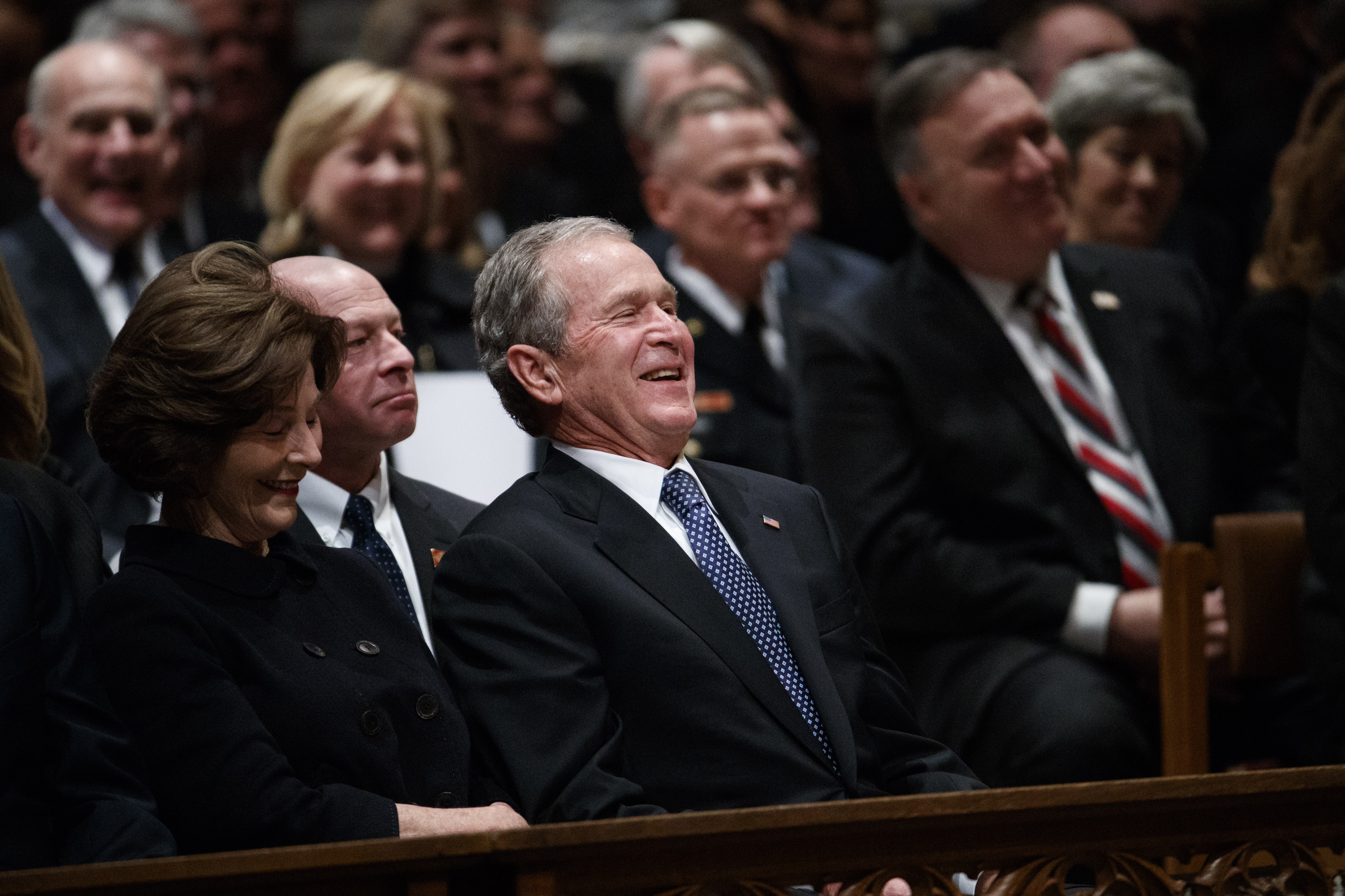 Former President George W. Bush and Laura Bush share a laugh as a story is told about his father, former President George H.W. Bush, during a State Funeral at the National Cathedral, Wednesday, Dec. 5, 2018, in Washington. (AP Photo/Evan Vucci)