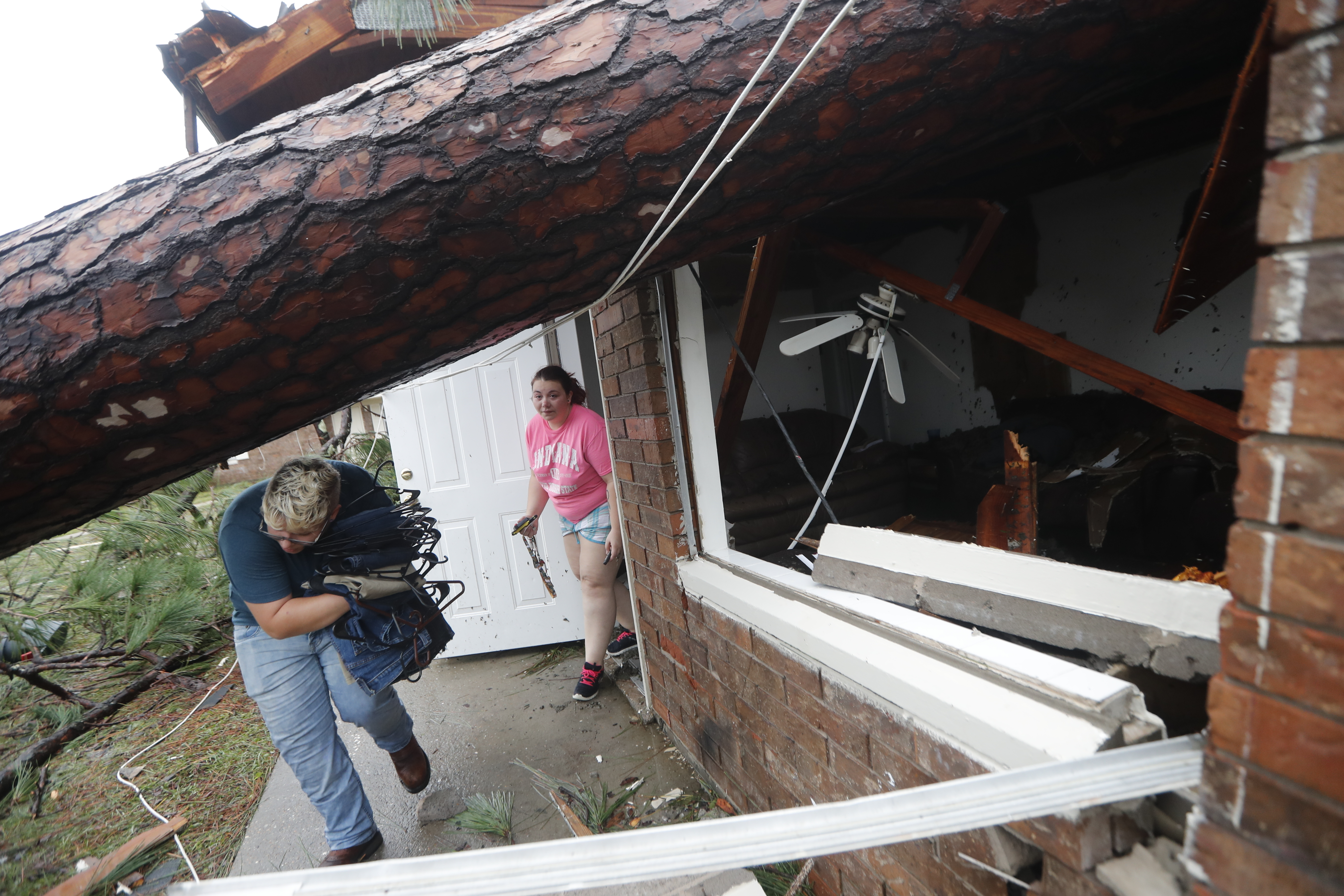Megan Williams, left, and roommate Kaylee O'Brian take belongings from their destroyed home after several trees fell on the house during Hurricane Michael in Panama City, Fla., Wednesday, Oct. 10, 2018. (AP Photo/Gerald Herbert)