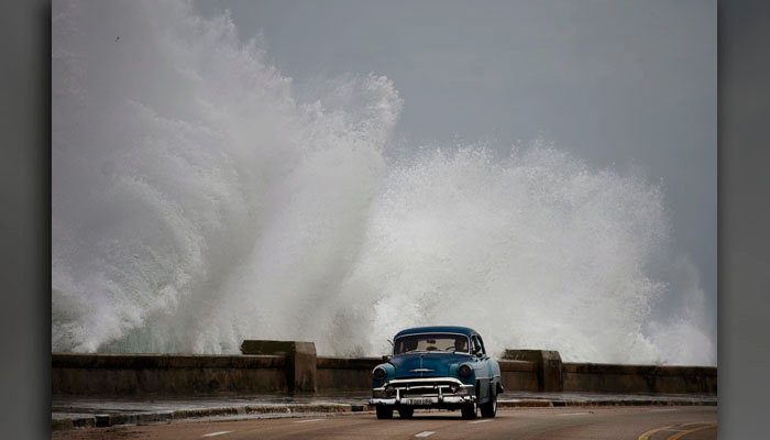 Waves crash against the Malecon, triggered by the outer bands of Hurricane Michael, as man drives past in a classic American car in Havana, Cuba, Tuesday, Oct. 9. (AP Photo/Ramon Espinosa)