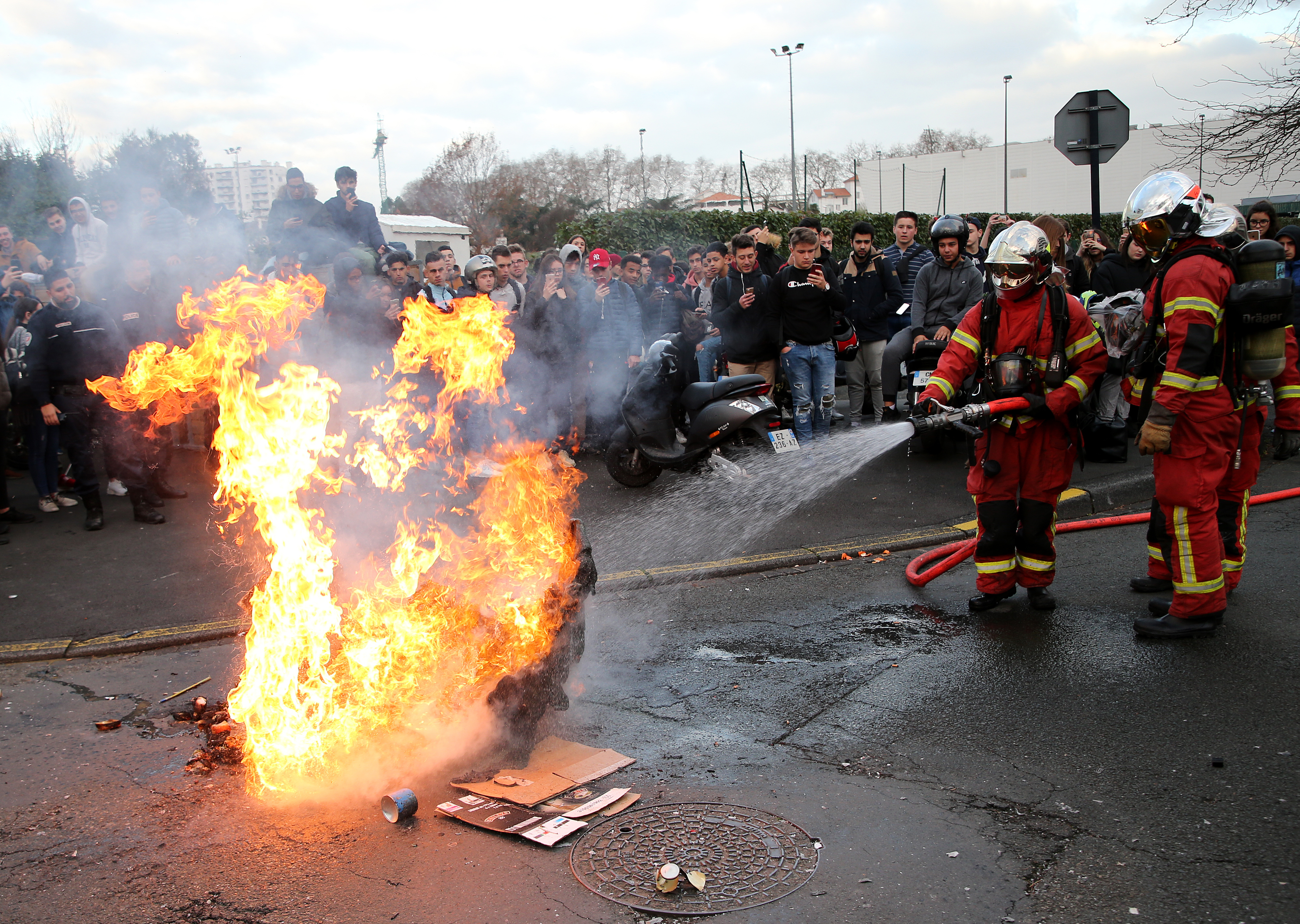Friefighters turn off fire on a burning trash bin outside a school in Bayonne, southwestern France, Thursday, Dec.6, 2018. Protesting students are disrupting schools and universities Thursday, and drivers are still blocking roads around France, now demanding broader tax cuts and government aid. (AP Photo/Bob Edme)