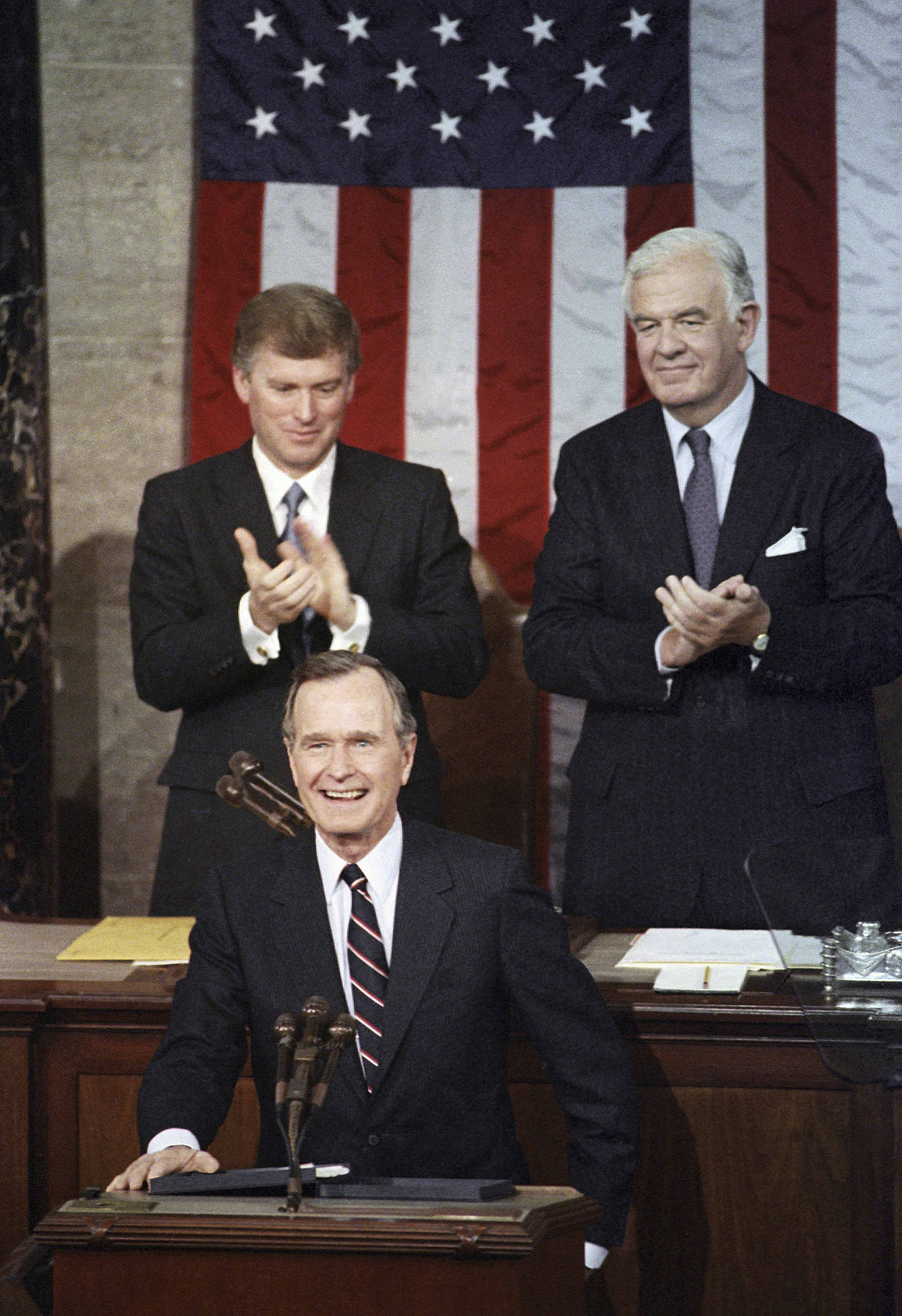 In this Jan. 31, 1990, photo, President George H.W. Bush receives applause from Vice President Dan Quayle, left, and House Speaker Thomas Foley prior to delivering his first State of the Union address on Capitol Hill in Washington. (AP Photo/Bob Daugherty, File)