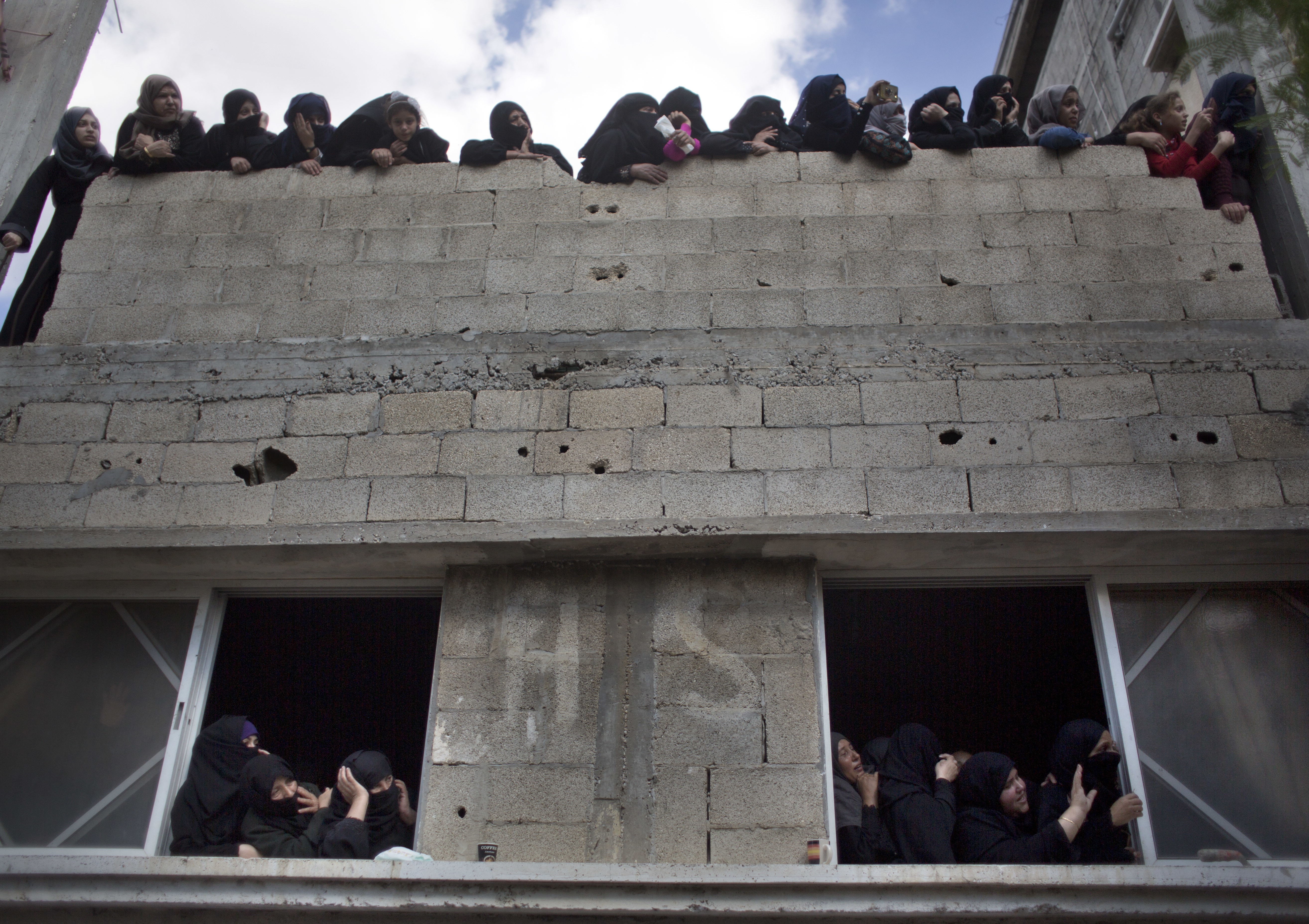Relatives of Ahmed Abu Lebdeh, 22, who was killed by Israeli troops during Friday's protest at the Gaza Strip's border with Israel, look at mourners carry his body out of the family home during his funeral in town of Khan Younis, southern Gaza Strip, Saturday, Oct. 27, 2018. (AP Photo/Khalil Hamra)