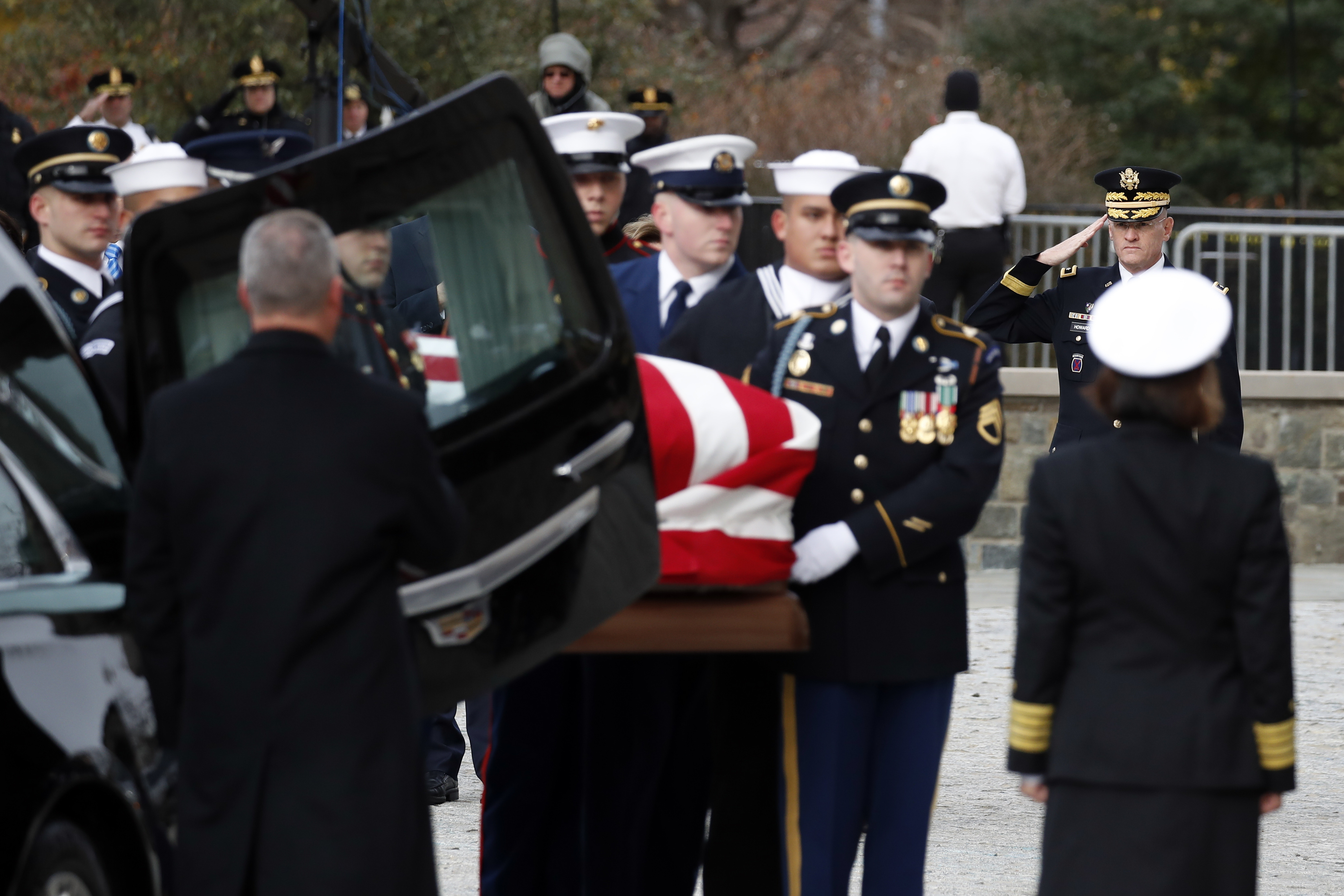 The flag-draped casket of former President George H.W. Bush is carried by a joint services military honor guard into a State Funeral at the National Cathedral, Wednesday, Dec. 5, 2018, in Washington. (AP Photo/Alex Brandon, Pool)