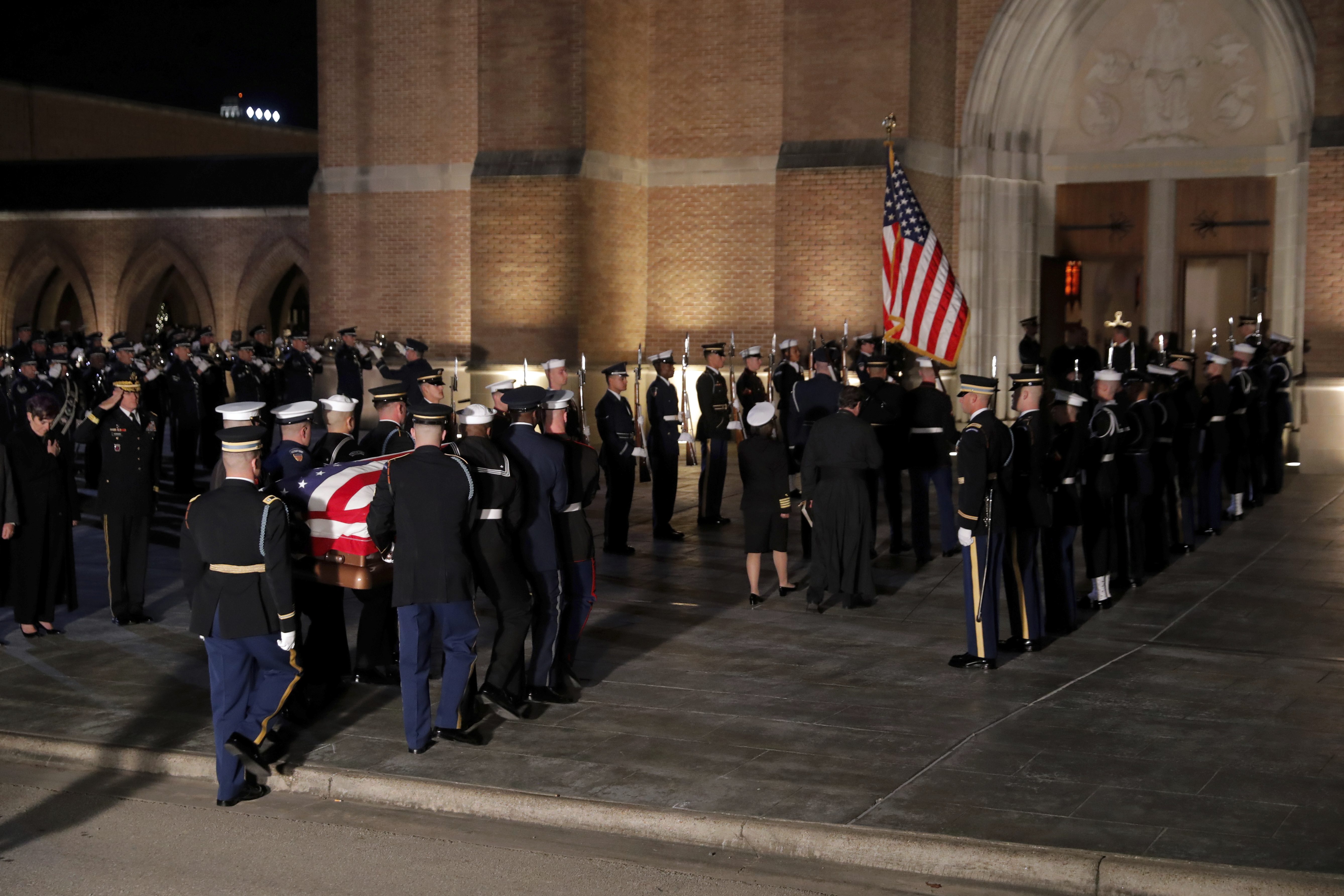 The flag-draped casket of former President George H.W. Bush is carried by a joint services military honor guard into St. Martin's Episcopal Church Wednesday, Dec. 5, 2018, in Houston. (AP Photo/Gerald Herbert)