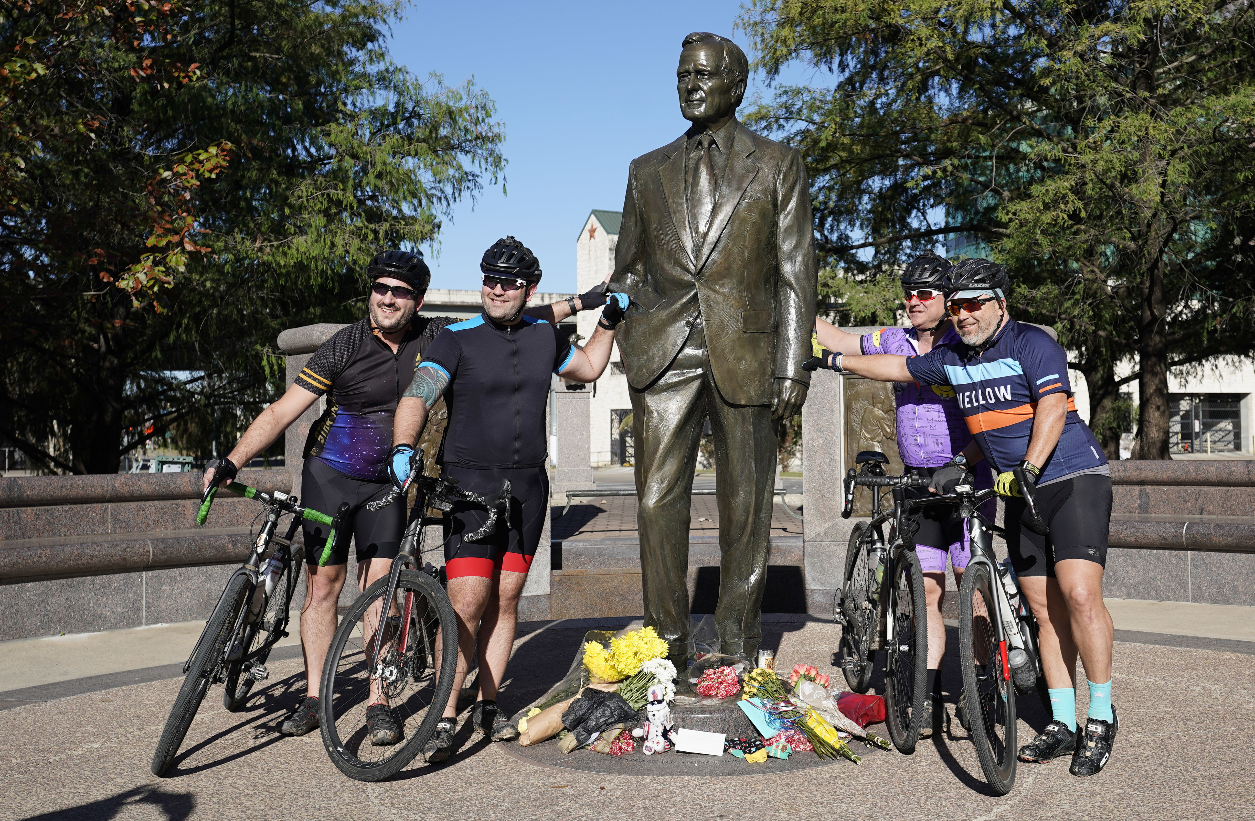A group of cyclists stop to have a picture taken with a statue of former President George H.W. Bush in downtown Houston, Sunday, Dec. 2. (AP Photo/David J. Phillip)
