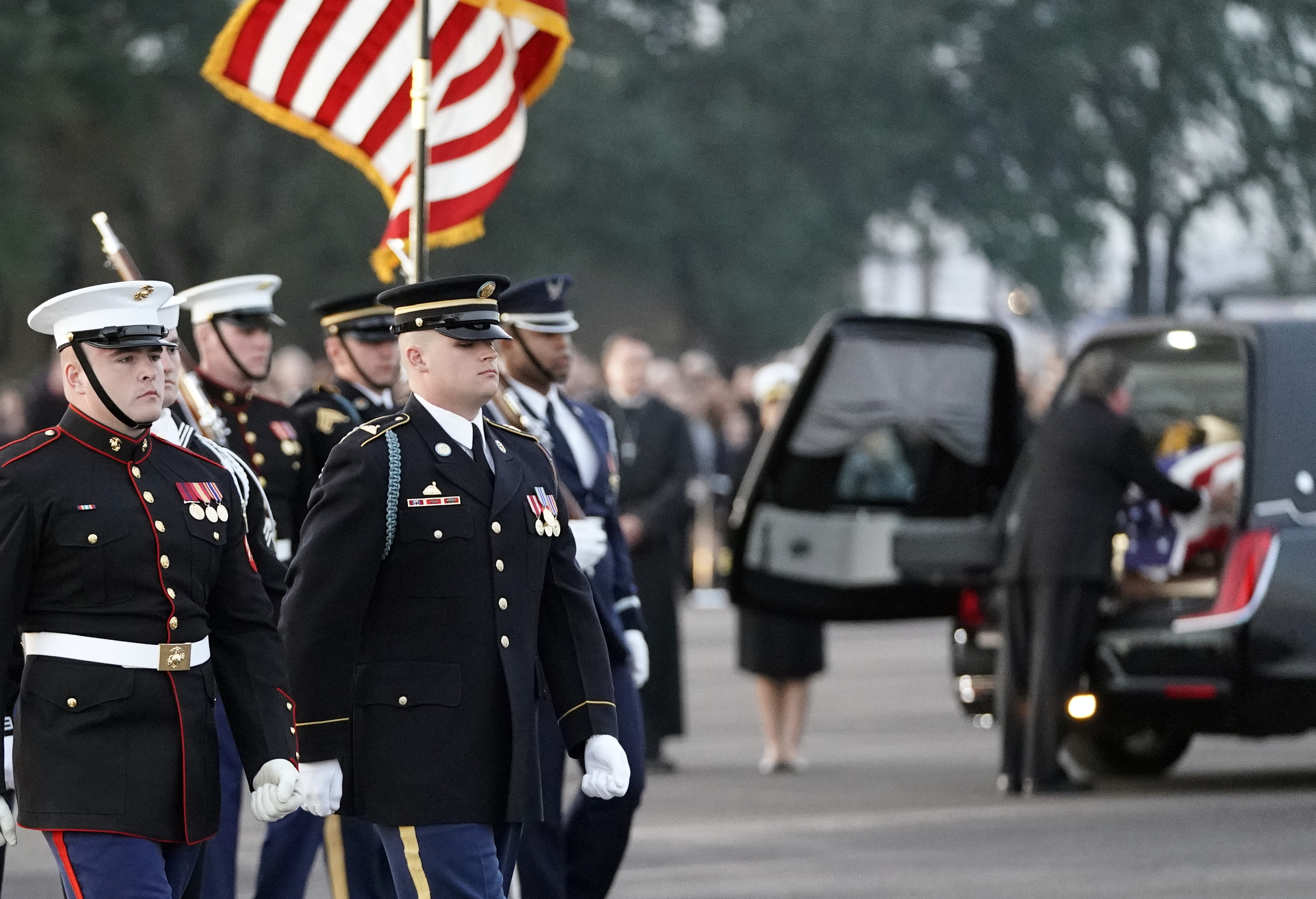 The flag-draped casket of former President George H.W. Bush is secured in a hearse after being carried by a joint services military honor guard Wednesday, Dec. 5, 2018, at Ellington Field in Houston. (AP Photo/David J. Phillip, Pool)