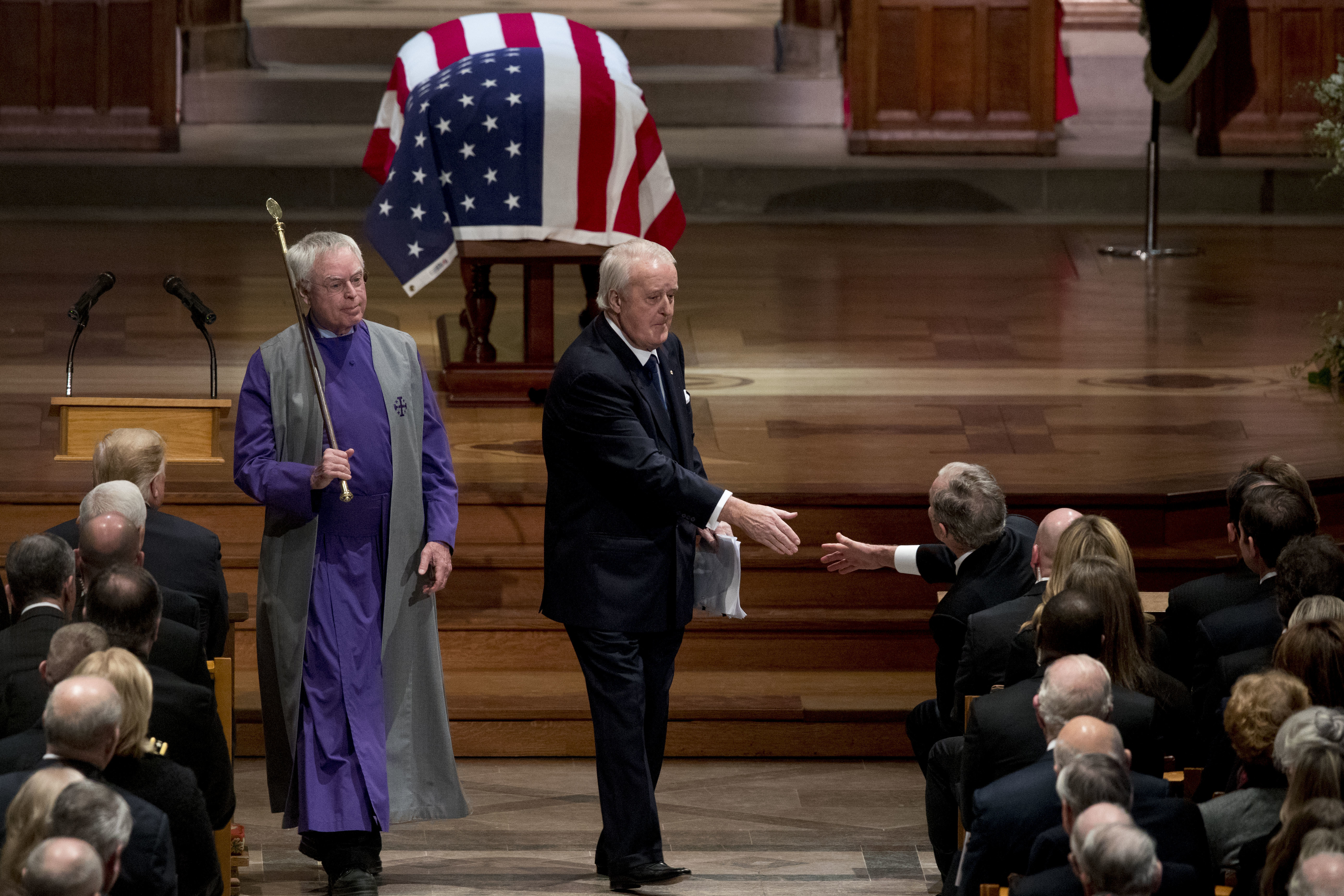 Former Canadian Prime Minister Brian Mulroney, center, shakes hands with former President George W. Bush, right, after speaking during the State Funeral for former President George H.W. Bush at the National Cathedral, Wednesday, Dec. 5, 2018, in Washington. (AP Photo/Andrew Harnik, Pool)