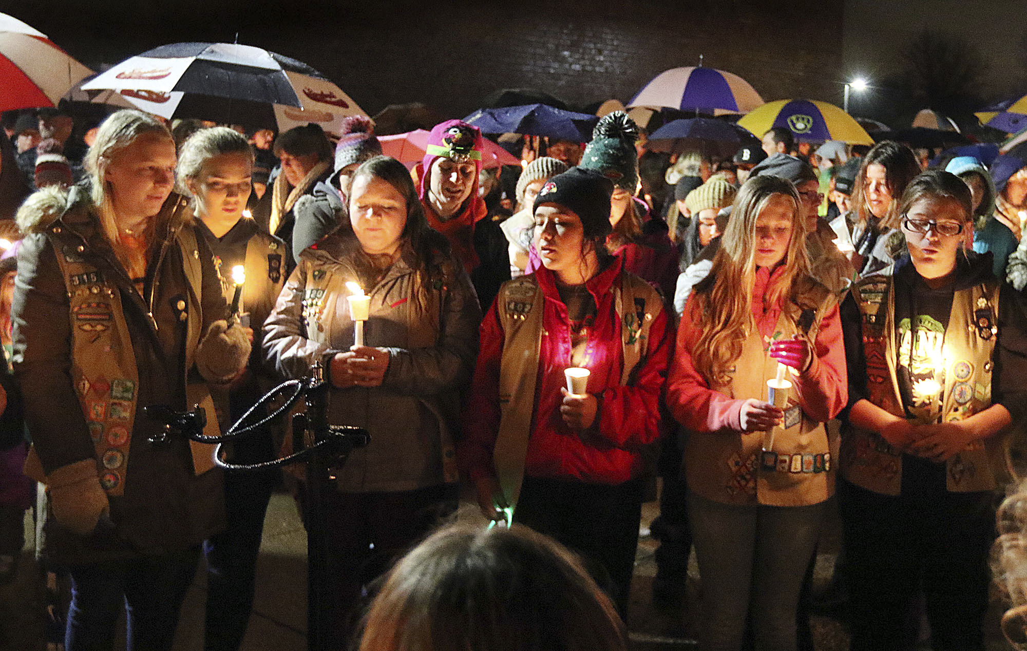 Girl Scouts sing as hundreds of community members turn out in the rain Sunday evening, Nov. 4, 2018, for a candlelight vigil at Halmstad Elementary School in Chippewa Falls, Wis., in remembrance of three fourth grade Girl Scouts and a parent who died Saturday, after being struck by a pickup truck while their troop was picking up trash along a rural highway. The 21-year-old driver, Colten Treu of Chippewa Falls, sped off but later surrendered. He will be charged with four counts of homicide, Lake Hallie police Sgt. Daniel Sokup said. (Steve Kinderman/The Eau Claire Leader-Telegram via AP)