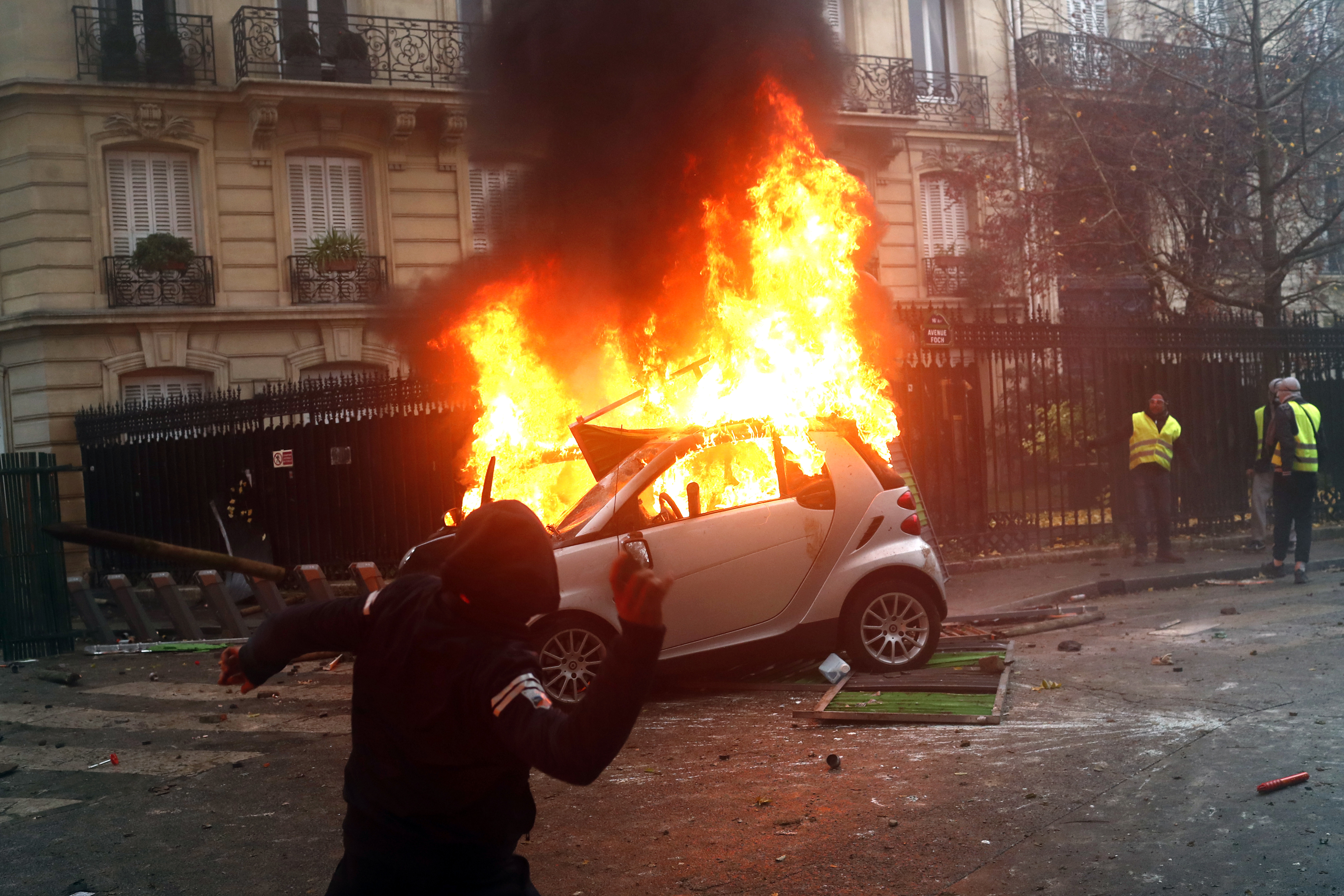 A hooded demonstrator throws an item as a car buns during a demonstration Saturday, Dec.1, 2018 in Paris. Protesters angry about rising taxes clashed with French police for a third straight weekend and over 100 were arrested after pockets of demonstrators built barricades in the middle of streets in central Paris, lit fires and threw rocks at officers Saturday. (AP Photo/Thibault Camus)