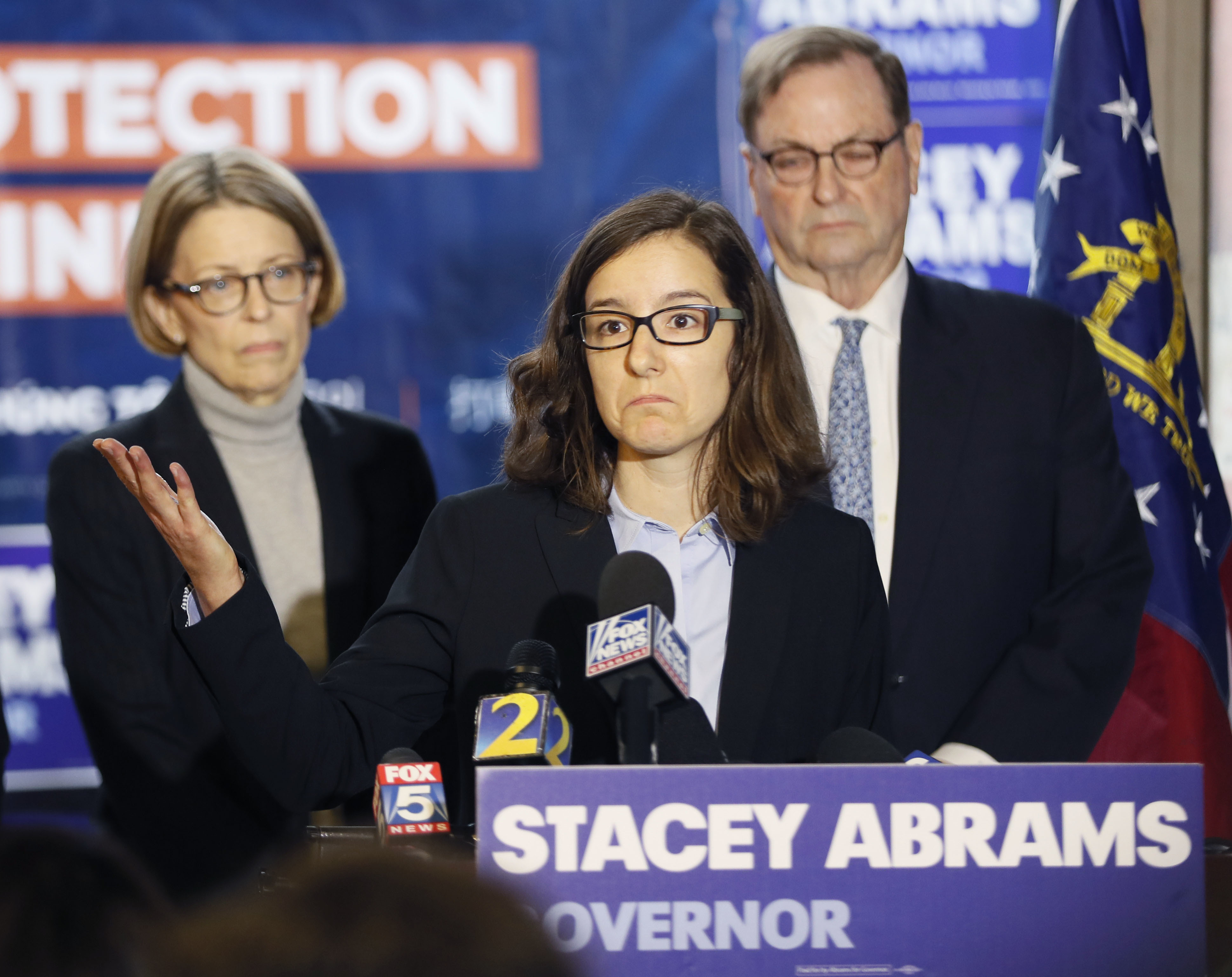 Lauren Groh-Wargo, Stacey Abrams' campaign manager, stands with attorneys at a news conference Thursday, Nov. 8, 2018, in Atlanta. Republican Brian Kemp resigned Thursday as Georgia's secretary of state, a day after his campaign said he's captured enough votes to become governor despite his rival's refusal to concede. Abrams' campaign immediately responded by refusing to accept Kemp's declaration of victory in the race and demanding that state officials